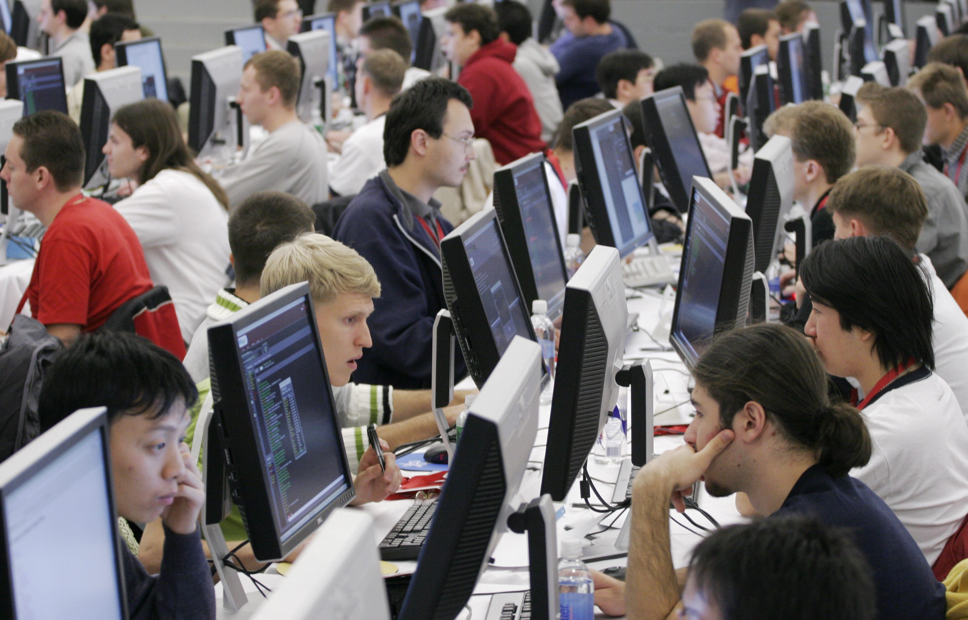 Contestants in the 2006 Google Global Code Jam stare at their computer screens at Google's New York office Friday, Oct. 27, 2006. One hundred of the best computer coders from around the world compete for prize money and bragging rights. The finalists from 20 countries are flown to New York by Google for the competition. (AP Photo/Mark Lennihan)