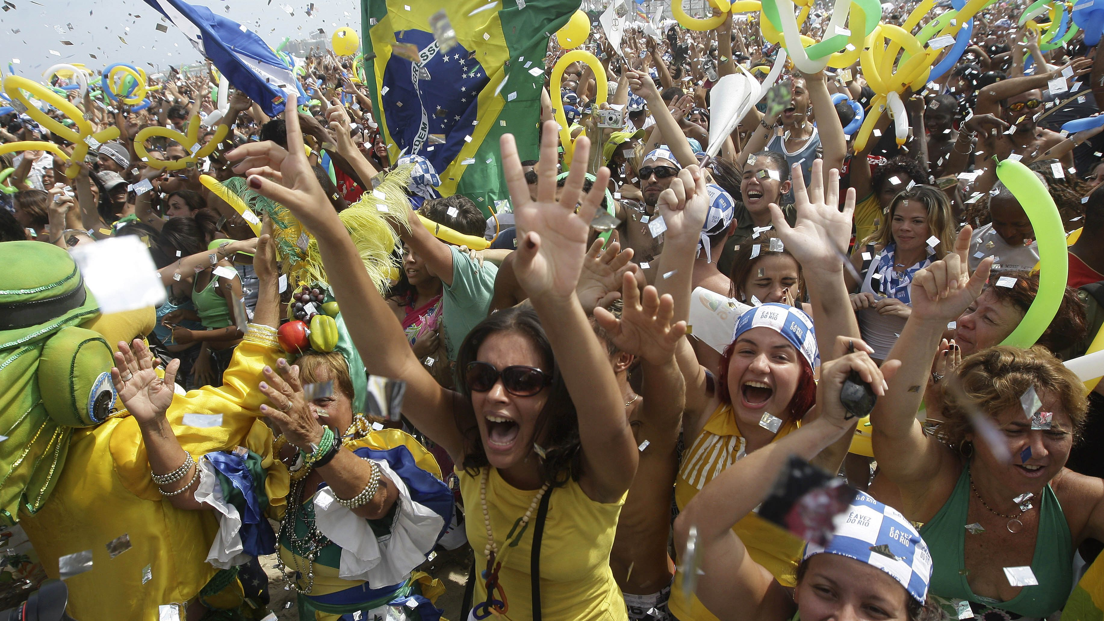 People celebrate after Rio de Janeiro won the nomination to host the 2016 Olympic Games at the Copacabana beach, in Rio de Janeiro, Friday, Oct. 2, 2009. Nearly 50,000 people erupted in celebration when Rio was announced host, jumping and cheering in a Carnival-like party on Copacabana beach. (AP Photo/Silvia Izquierdo)