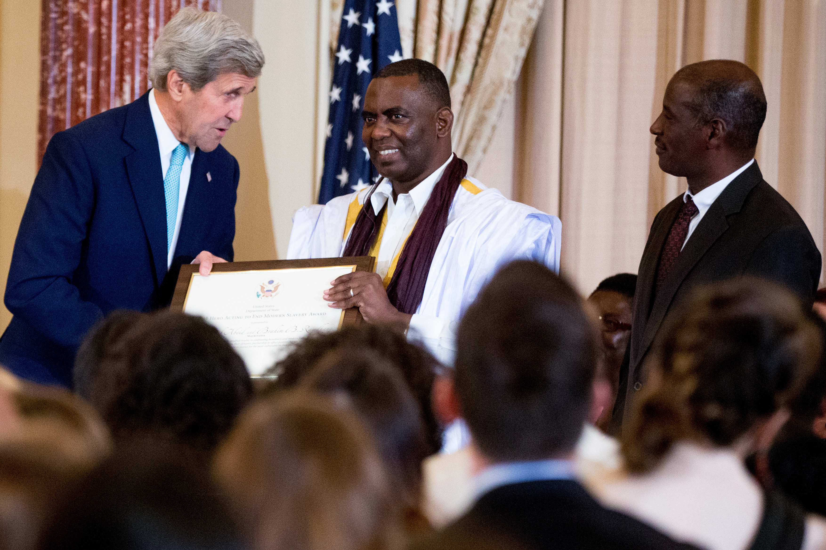 """US Secretary of State John Kerry with anti-slavery activist Biram Dah Abeid, center, and Brahim Bilal Ramdhane, right, of Mauritania as they are recognized as """"2016 Trafficking in Persons Report"""" heroes, whose efforts have made an impact on the global fight against modern slavery, Thursday, June 30, 2016, during a news conference for the report in the Ben Franklin Room of the State Department in Washington."""