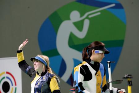 Virginia Thrasher, left, of the United States waves after she won the gold medal for the Women's 10m Air Rifle competition ash runner up Du li, right, of China walks way from the shooting position at Olympic Shooting Center at the 2016 Summer Olympics in Rio de Janeiro, Brazil, Saturday, Aug. 6, 2016.