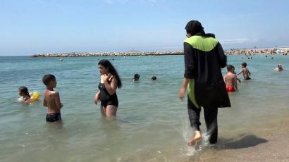 In this Aug.4 2016 file photo made from video, Nissrine Samali, 20, gets into the sea wearing traditional Islamic dress, in Marseille, southern France. The French resort of Cannes has banned full-body, head-covering swimsuits worn by some Muslim women from its beaches, citing security concerns. A City Hall official said the ordinance, in effect for August, could apply to burkini-style swimsuits. (AP Photo, File)