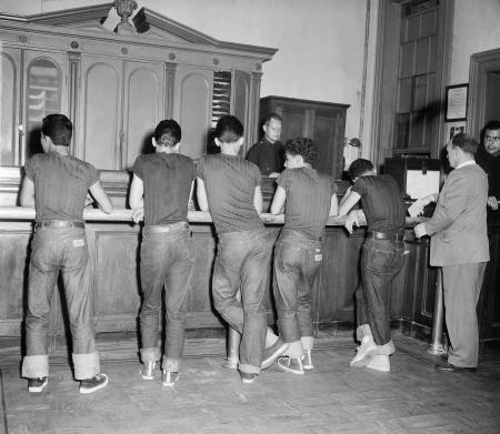 "Five boys, all wearing blue jeans and the same dark shirt, stand in front of booking officer at the west 47th street police station in New York, July 31, 1954. The youths were among some 90 persons picked up by police in a drive on juvenile delinquents and ""generally undesirable characters."" All were round up in Time Square area. (AP Photo/Chris Daly)"