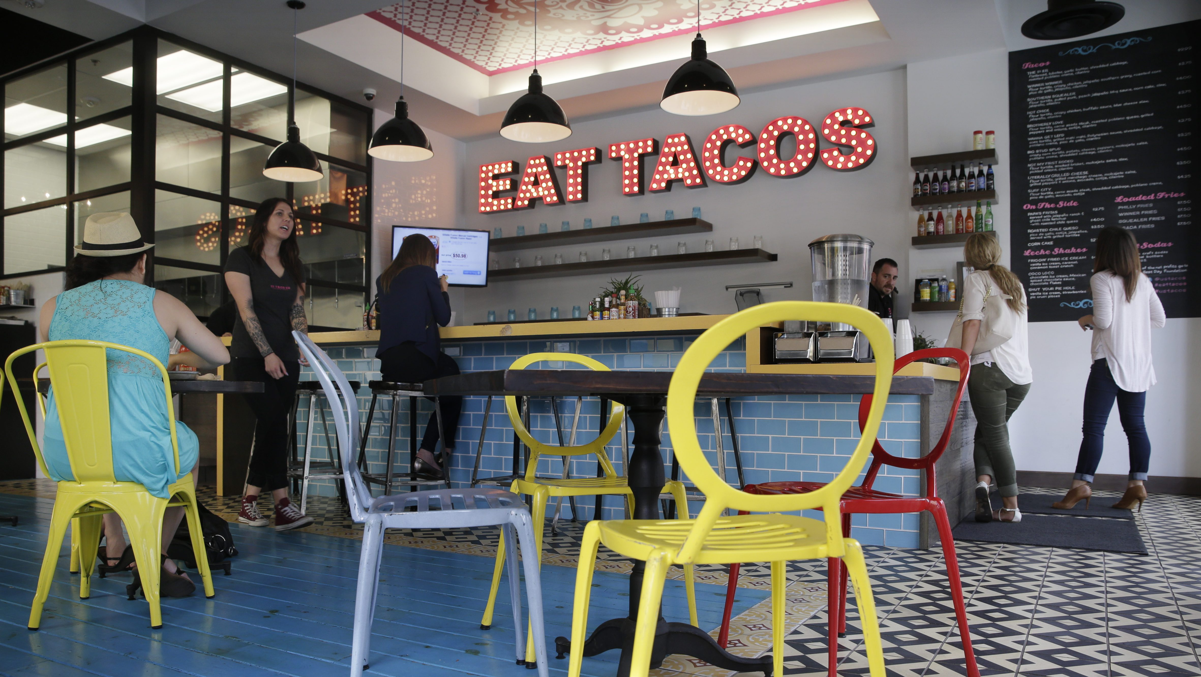 In this Feb. 20, 2015 photo, diners eat at U.S. Taco Co., which is owned by Taco Bell, in Huntington Beach, Calif. As people increasingly reach for foods that stray from the norm and seem less processed, some companies are testing whether it would pay to tuck away their famous logos in favor of more hipster guises. (AP Photo/Jae C. Hong)