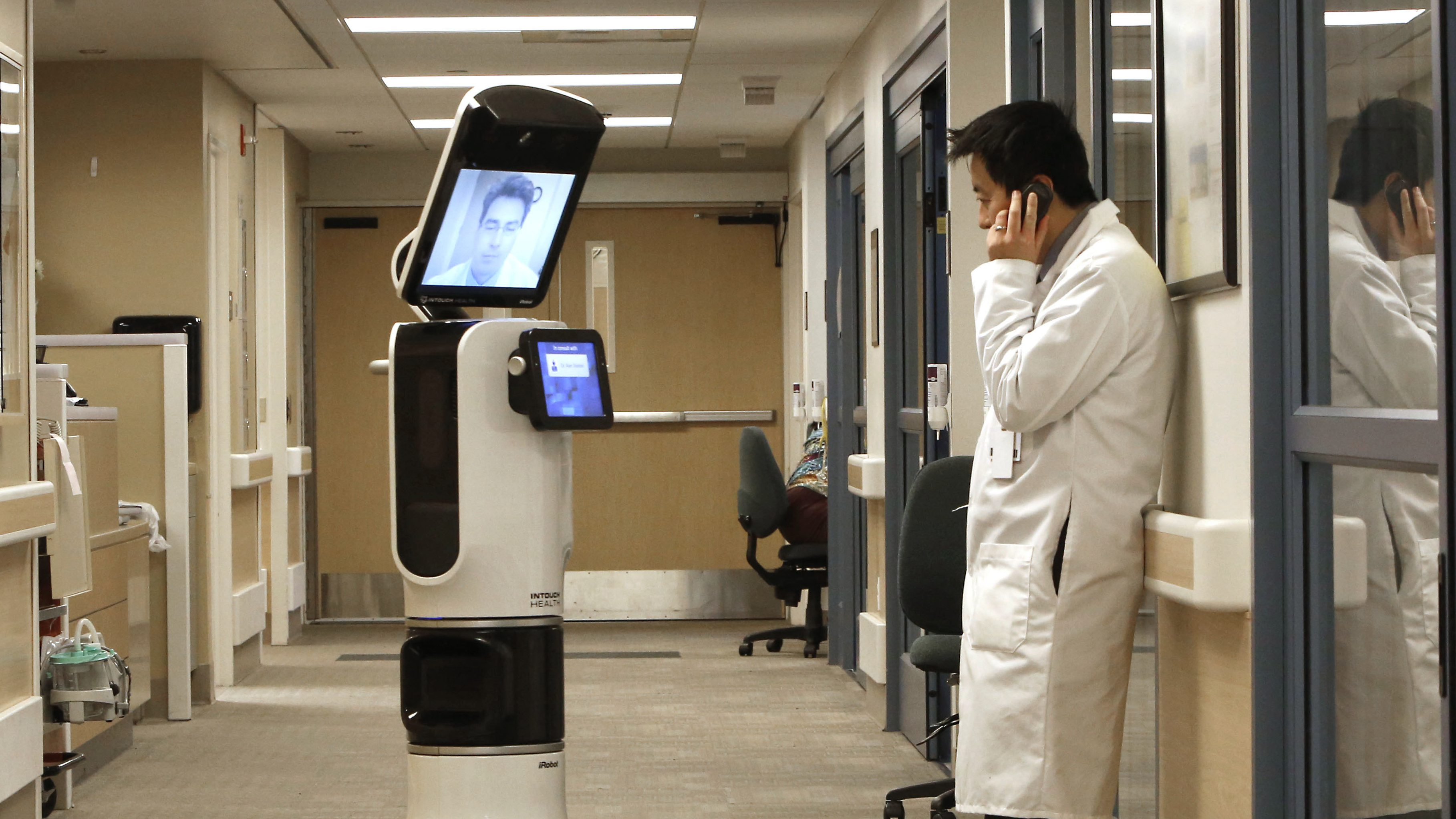 """In this photo taken Wednesday, Nov. 6, 2013 Dr. Alan Shatzel, medical director of the Mercy Telehealth Network, is displayed on the monitor RP-VITA robot as he waits to confer with Dr. Alex Nee at Mercy San Juan Hospital in Carmichael, Calif. The robots enable physicians to have  """"beam"""" themselves into hospitals to diagnose patients and offer medical advice during emergencies."""