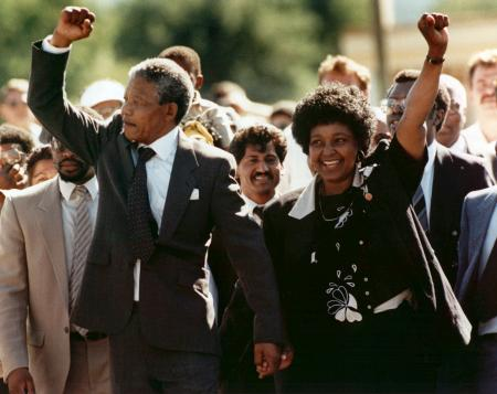 FILE - In this Feb. 11, 1990 file photo, Nelson Mandela, left, and his wife Winnie, raise clenched fists as they walk hand-in-hand from the Victor Verster prison near Cape Town, South Africa. South Africans are marking the anniversary of the release of the country's first black president, Nelson Mandela, who was freed 25 years ago. Mandela was released on Feb. 11, 1990, after 27 years in prison. (AP Photo/Greg English, File)
