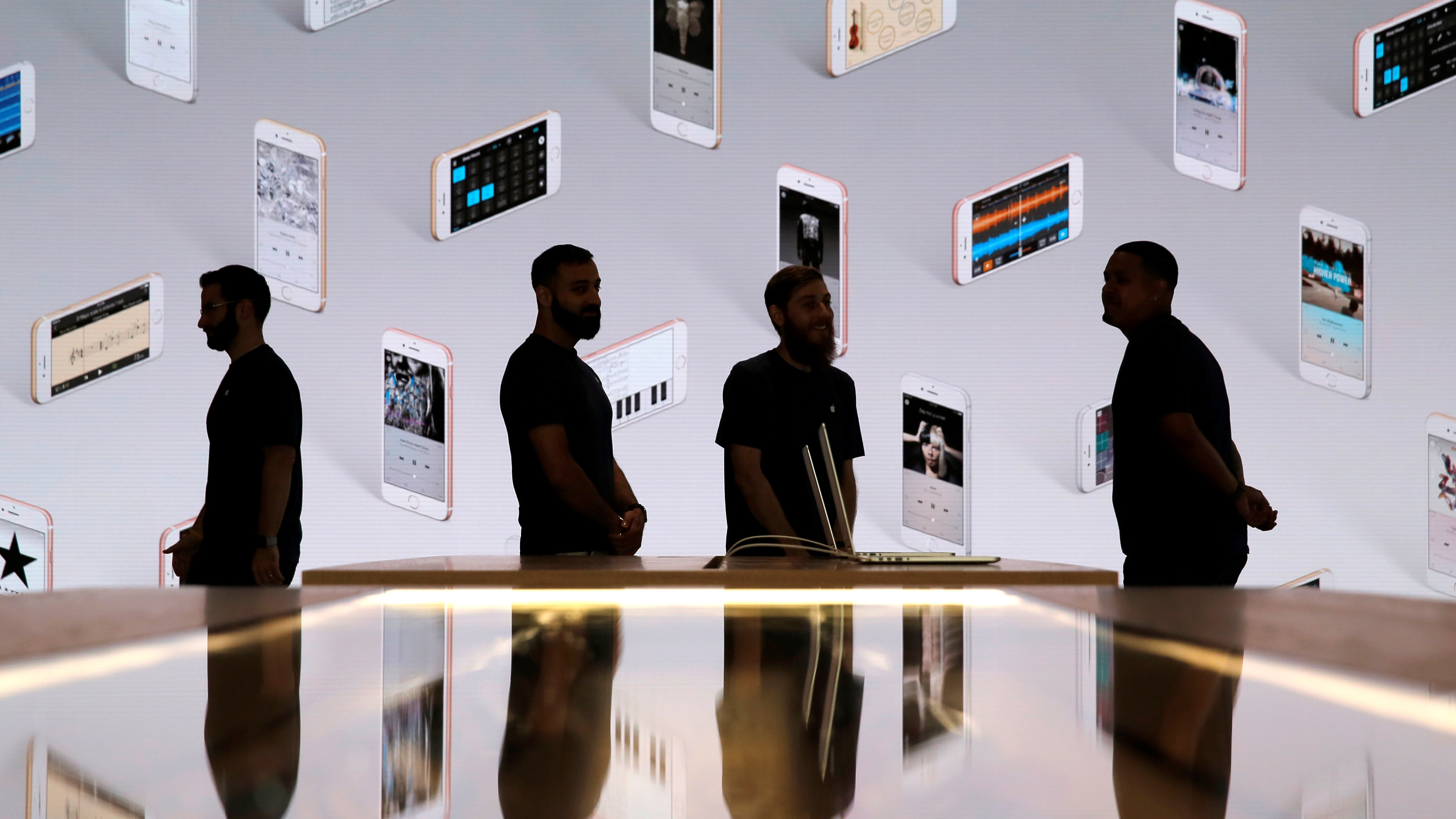 Store employees stand in front of a screen displaying iPhones during a preview event at the new Apple Store Williamsburg in Brooklyn, New York, U.S., July 28, 2016.  REUTERS/Andrew Kelly  - RTSK4MH