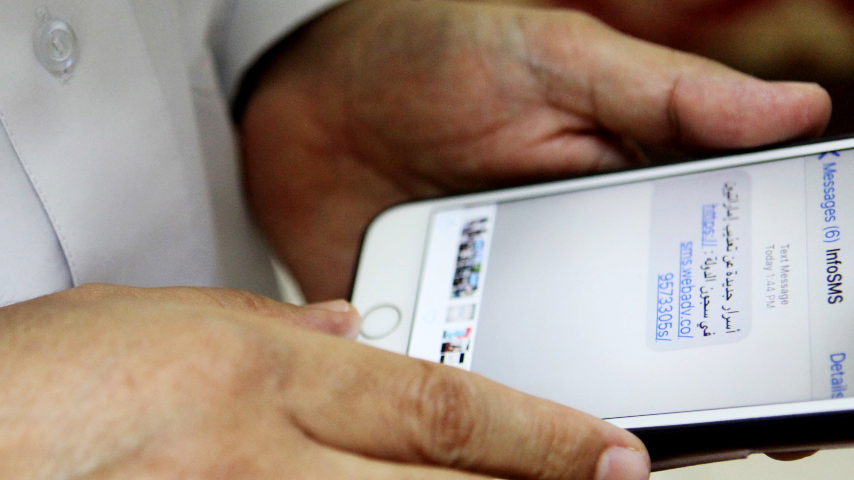 """Human rights activist Ahmed Mansoor shows Associated Press journalists a screenshot of a spoof text message he received in Ajman, United Arab Emirates, on Thursday, Aug. 25, 2016. Mansoor was recently targeted by spyware that can hack into Apple's iPhone handset. The company said Thursday it was updated its security. The text message reads: """"New secrets on the torture of Emirati citizens in jail."""" (AP Photo/Jon Gambrell)"""