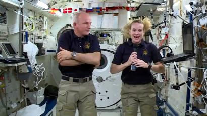 """In this image made from video provided by NASA, astronaut Kate Rubins, right, speaks during an interview aboard the International Space Station on Wednesday, July 13, 2016. At left is Expedition 48 Commander Jeff Williams. Rubins will attempt to complete the first full-blown DNA decoding, or """"sequencing,"""" in orbit. The device will be delivered to the International Space Station in the next SpaceX delivery."""