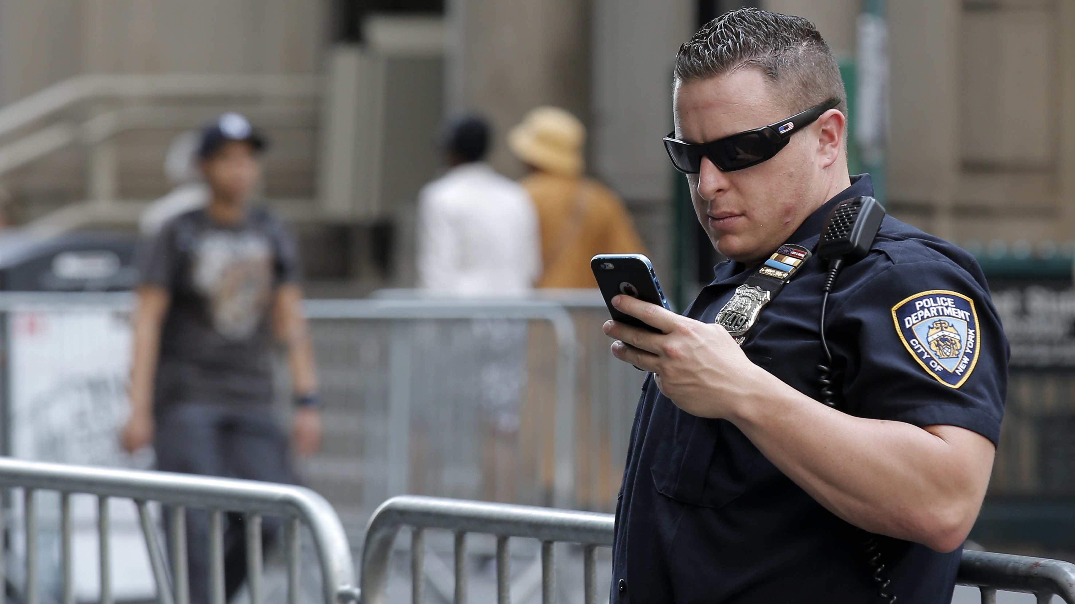A New York City Police Department (NYPD) officer uses his iPhone while on duty in New York