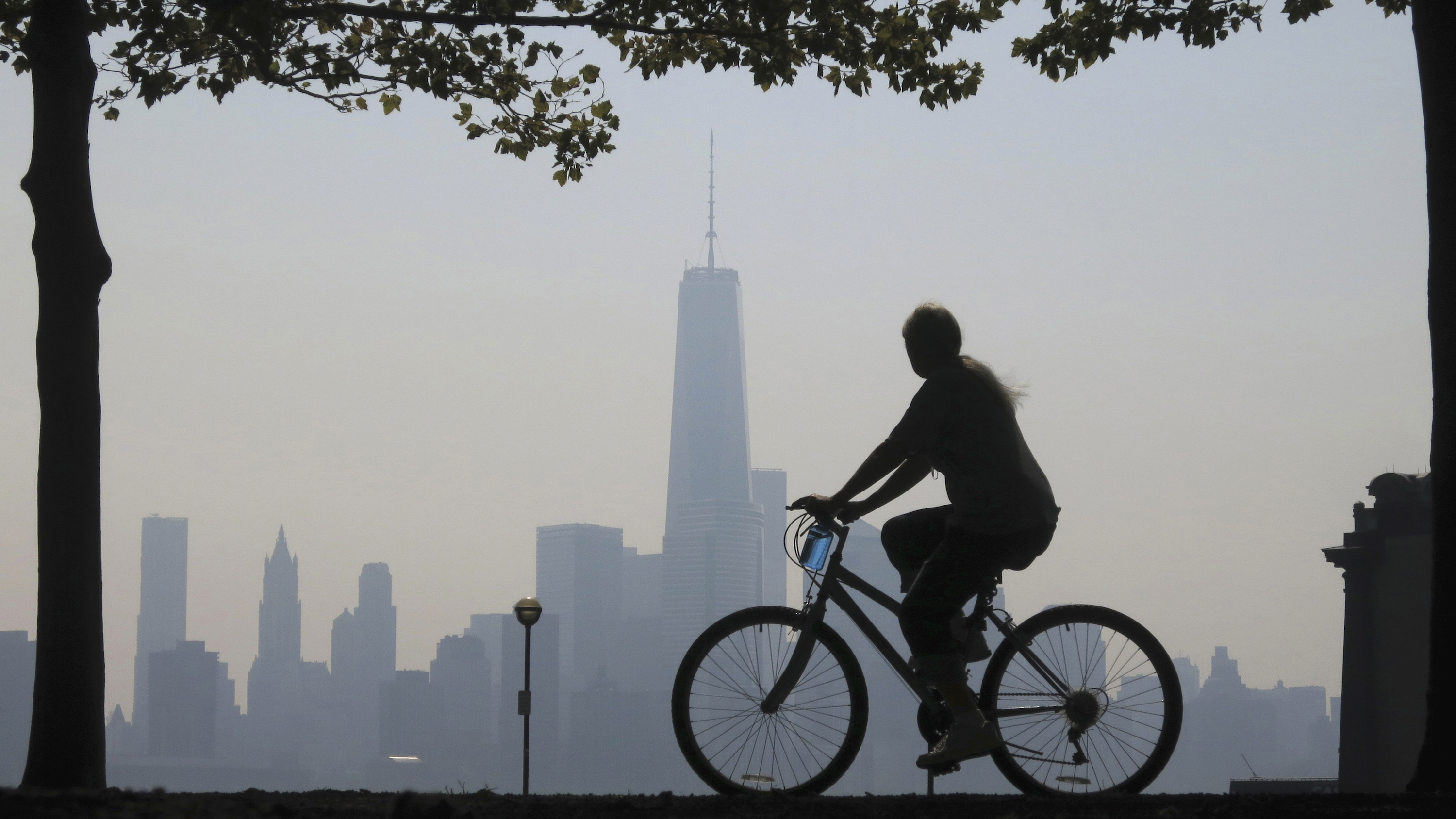 A woman rides bicycle past New York skyline, at a park in New Jersey