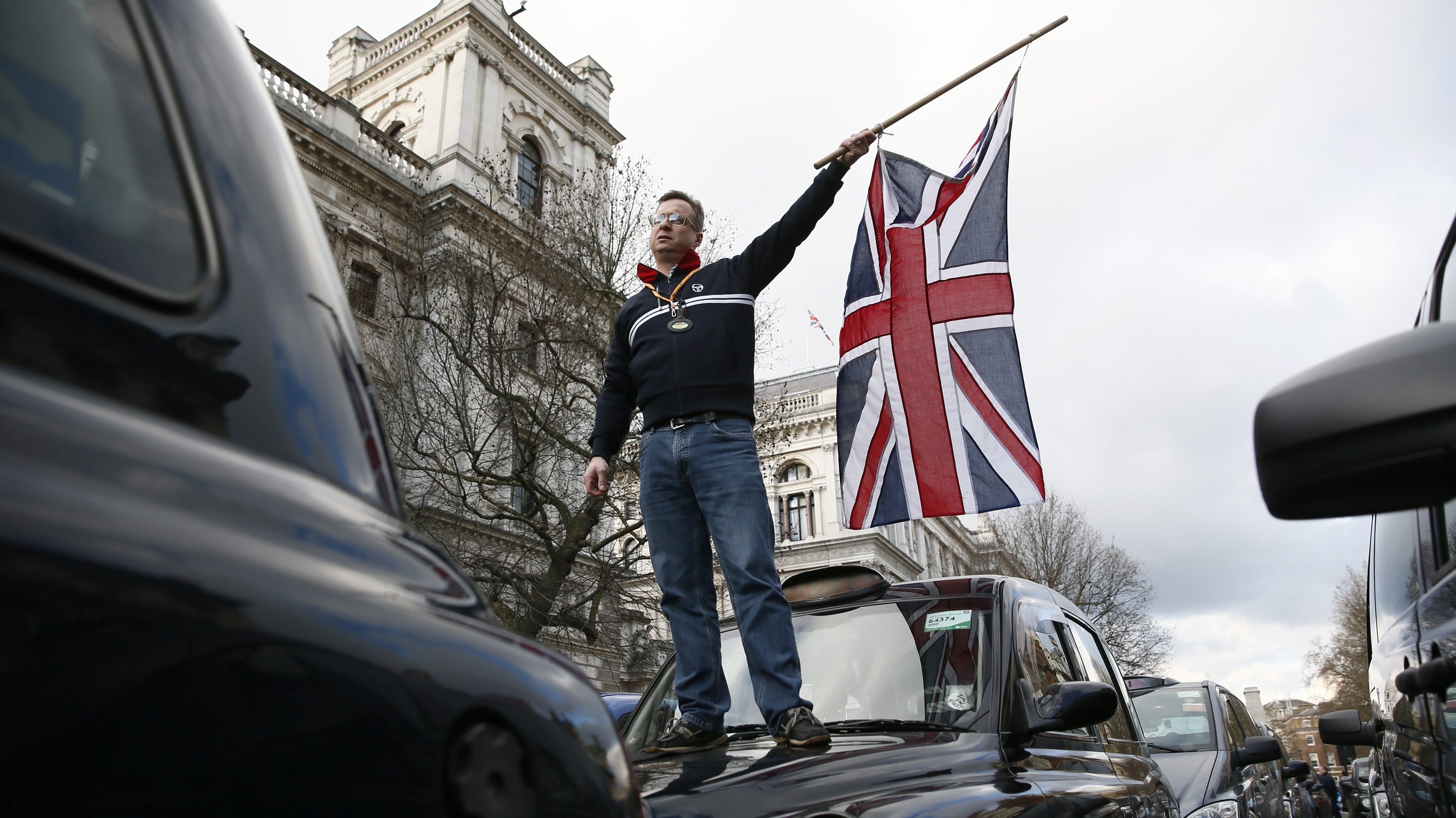 A London cab driver waves a Union flag as he stands on the bonnet of his taxi during a protest against Uber on Whitehall in central London, February 10, 2015 REUTERS/Stefan Wermuth - RTX26CG6