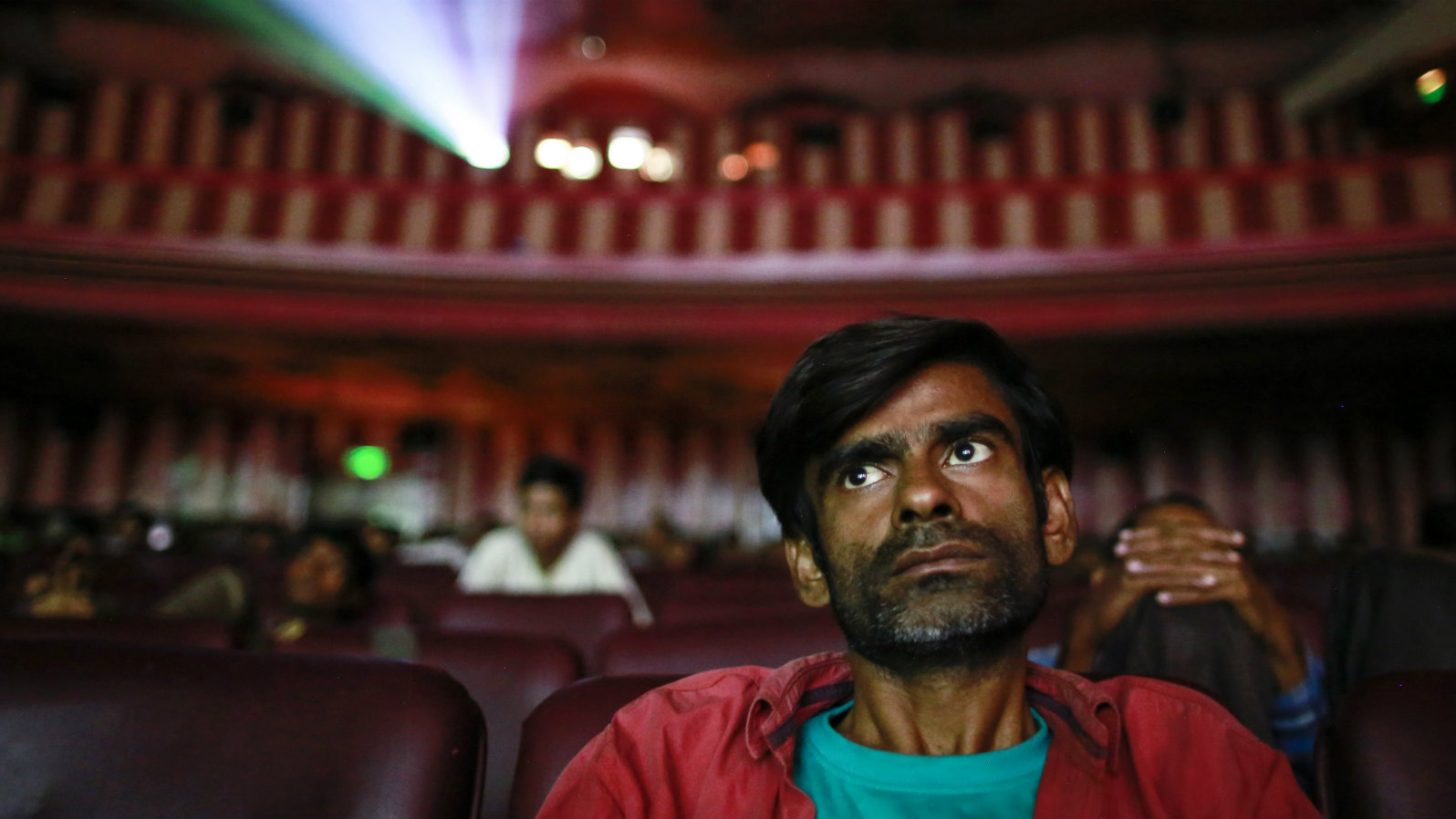 "Cinema goers watch Bollywood movie ""Dilwale Dulhania Le Jayenge"" (The Big Hearted Will Take the Bride), starring actor Shah Rukh Khan, inside Maratha Mandir theatre in Mumbai December 11, 2014. The movie, released in October 1995, has set a record of completing 1000 weeks of continuous screening at a cinema, a feat unmatched by any other Bollywood movies. According to Manoj Desai, owner of the theatre, the movie, which is still being screened, enjoys at least 50 to 60 percent occupancy on weekdays and full house on weekends at his theatre. The movie is screened only in the morning and the ticket price ranges from 15 to 20 Indian rupees ($0.24-$0.32). Picture taken December 11, 2014."