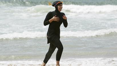 Woman in a burkini on the beach.