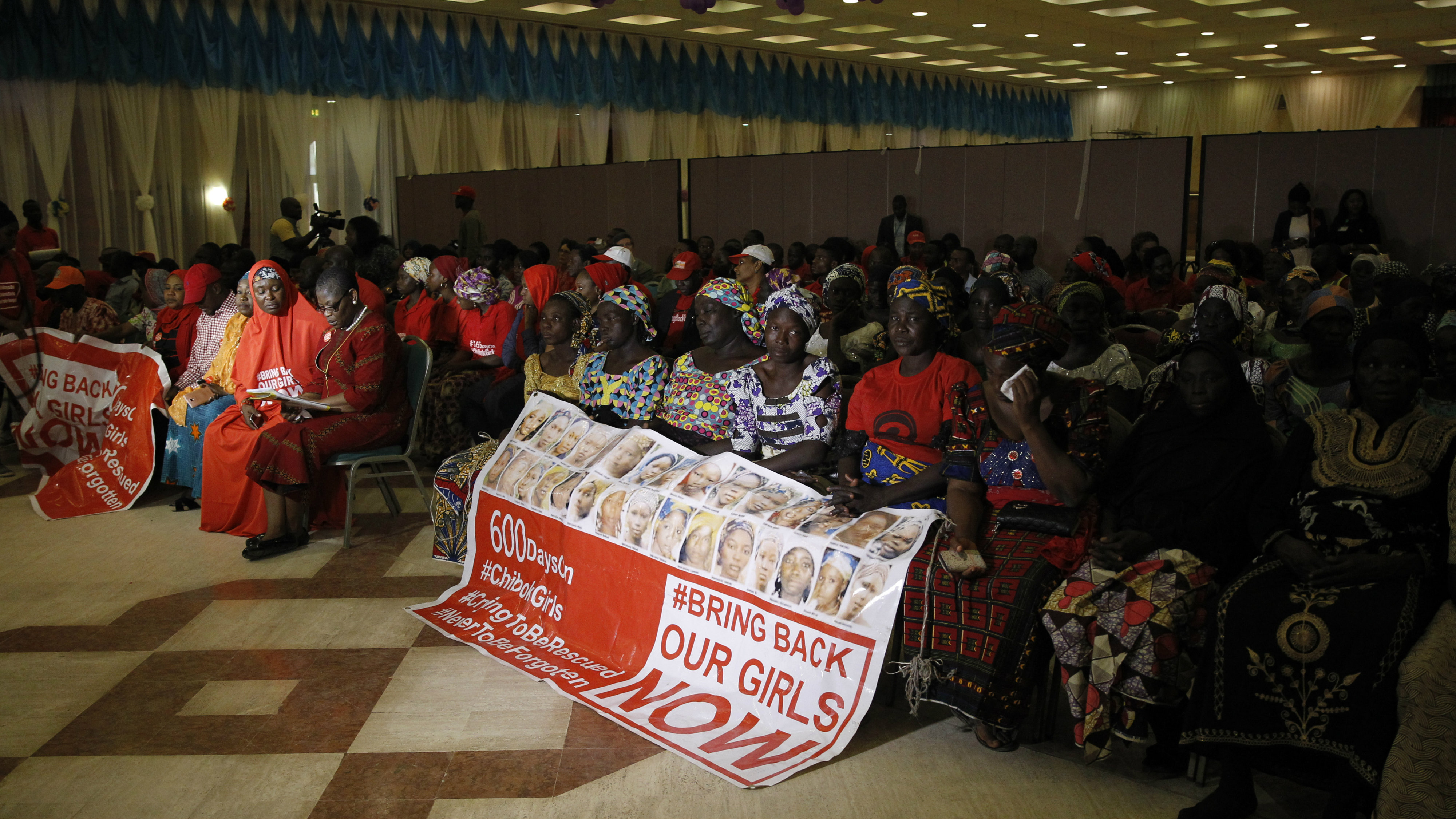 """Parents of the Chibok girls hold a """"Bring Back Our Girls"""" banner during their meeting with Nigeria's President Muhammadu Buhari at the presidential villa in Abuja, Nigeria, January 14, 2016."""