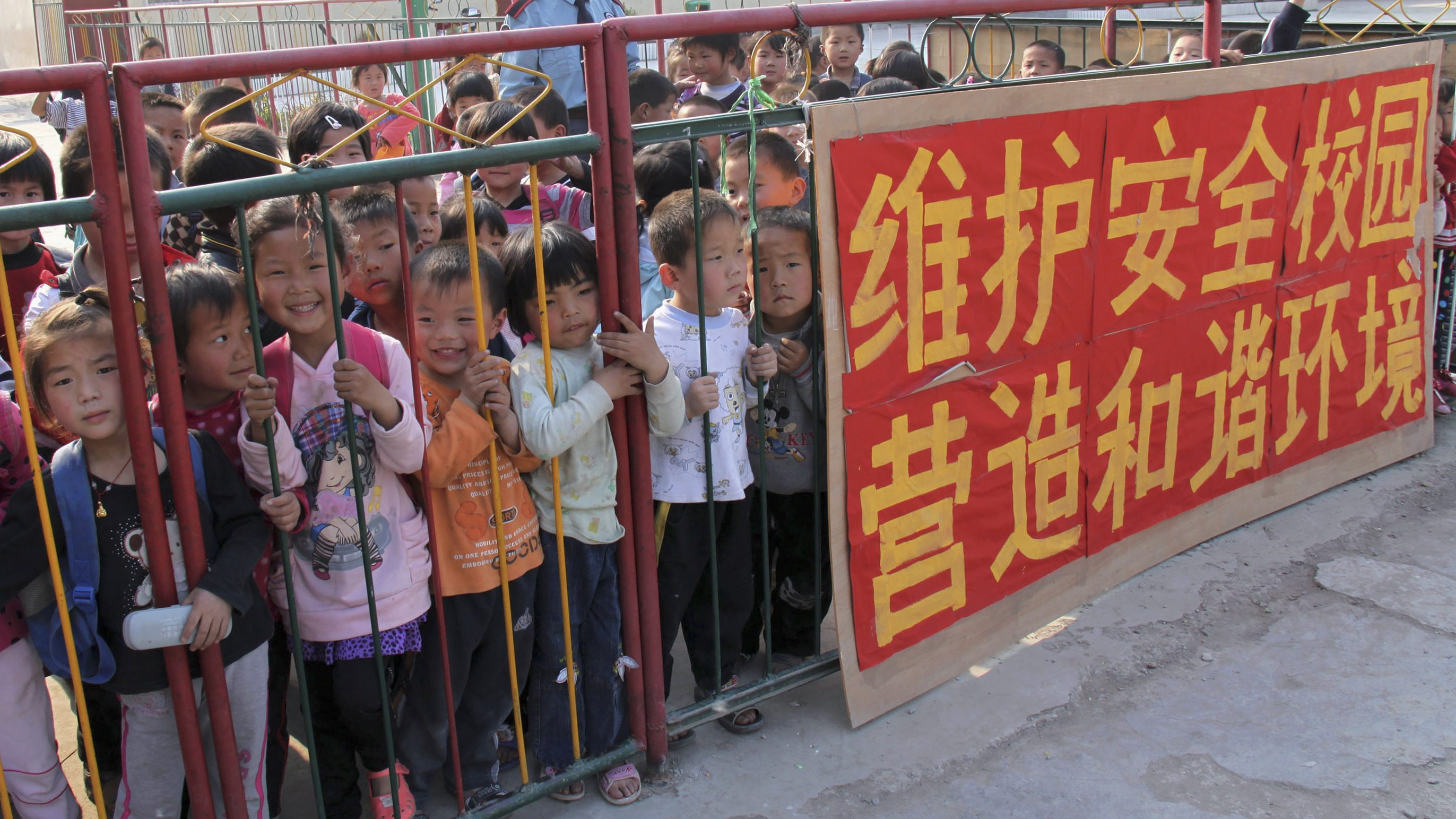 """Children wait behind fence for their parents after school at a kindergarten in Tangying County, Henan province May 13, 2010. A spate of school killings in China has """"deep-seated"""" roots in the country's social tensions which need addressing, Premier Wen Jiabao said. The Chinese characters read, """"maintain school security and create a harmonious environment""""."""