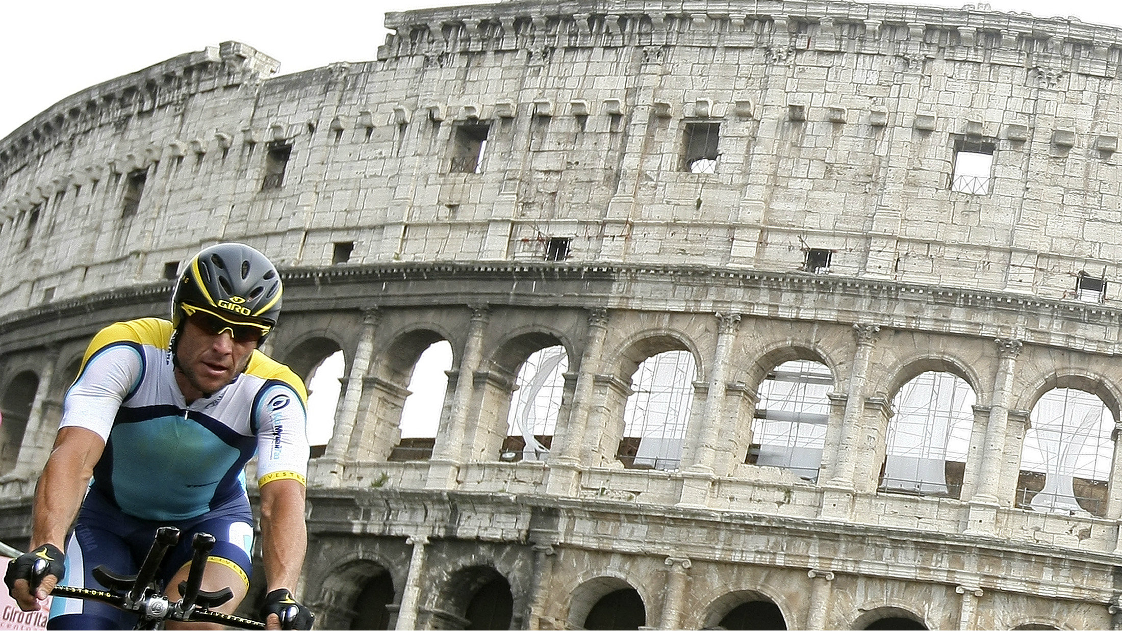 Lance Armstrong biking in front of the Colloseum.