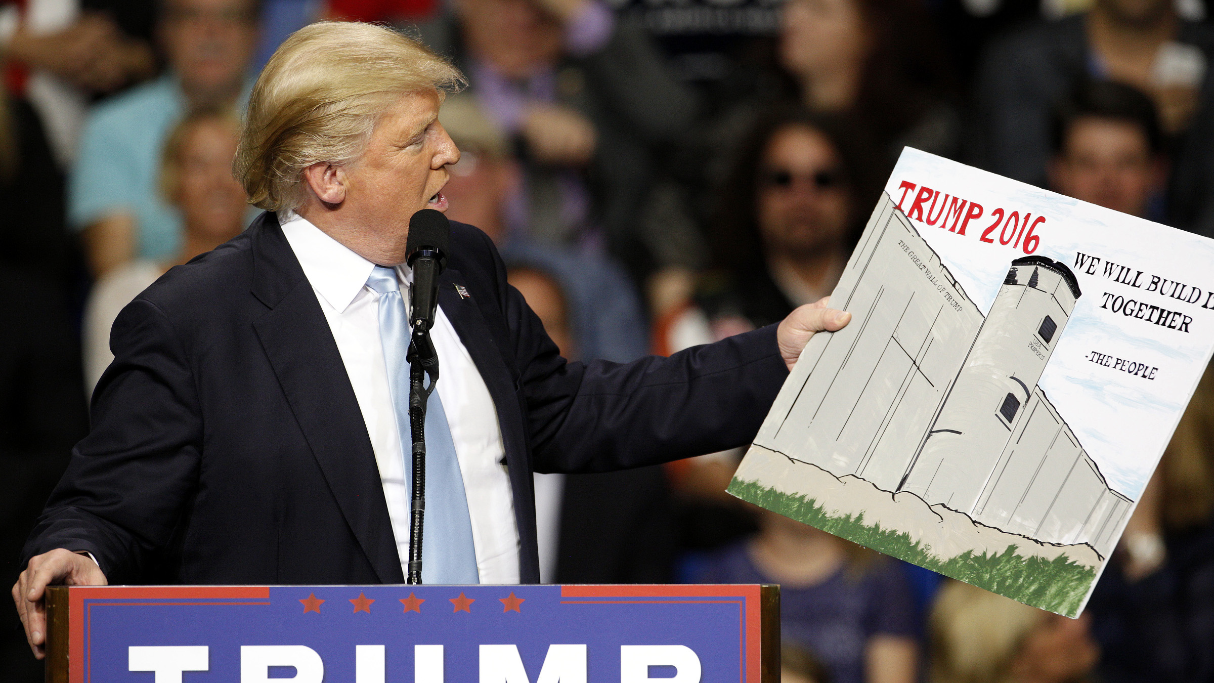 U.S. Republican presidential candidate Donald Trump holds a sign supporting his plan to build a wall between the United States and Mexico that he borrowed from a member of the audience at his campaign rally in Fayetteville, North Carolina March 9, 2016. Trump was interrupted repeatedly by demonstrators during his rally.
