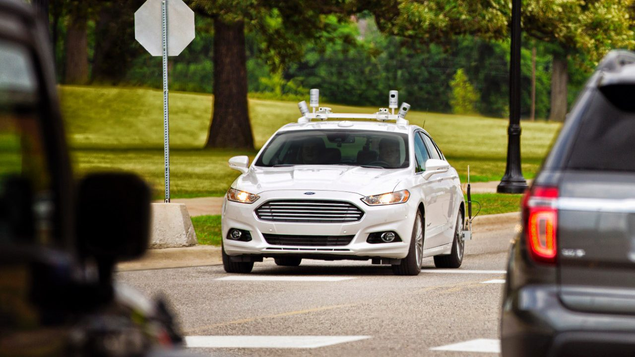 A Ford Fusion sedan outfitted with lidar cameras is seen on the road