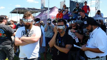 Pilots at the drone nationals watch a race through video goggles.