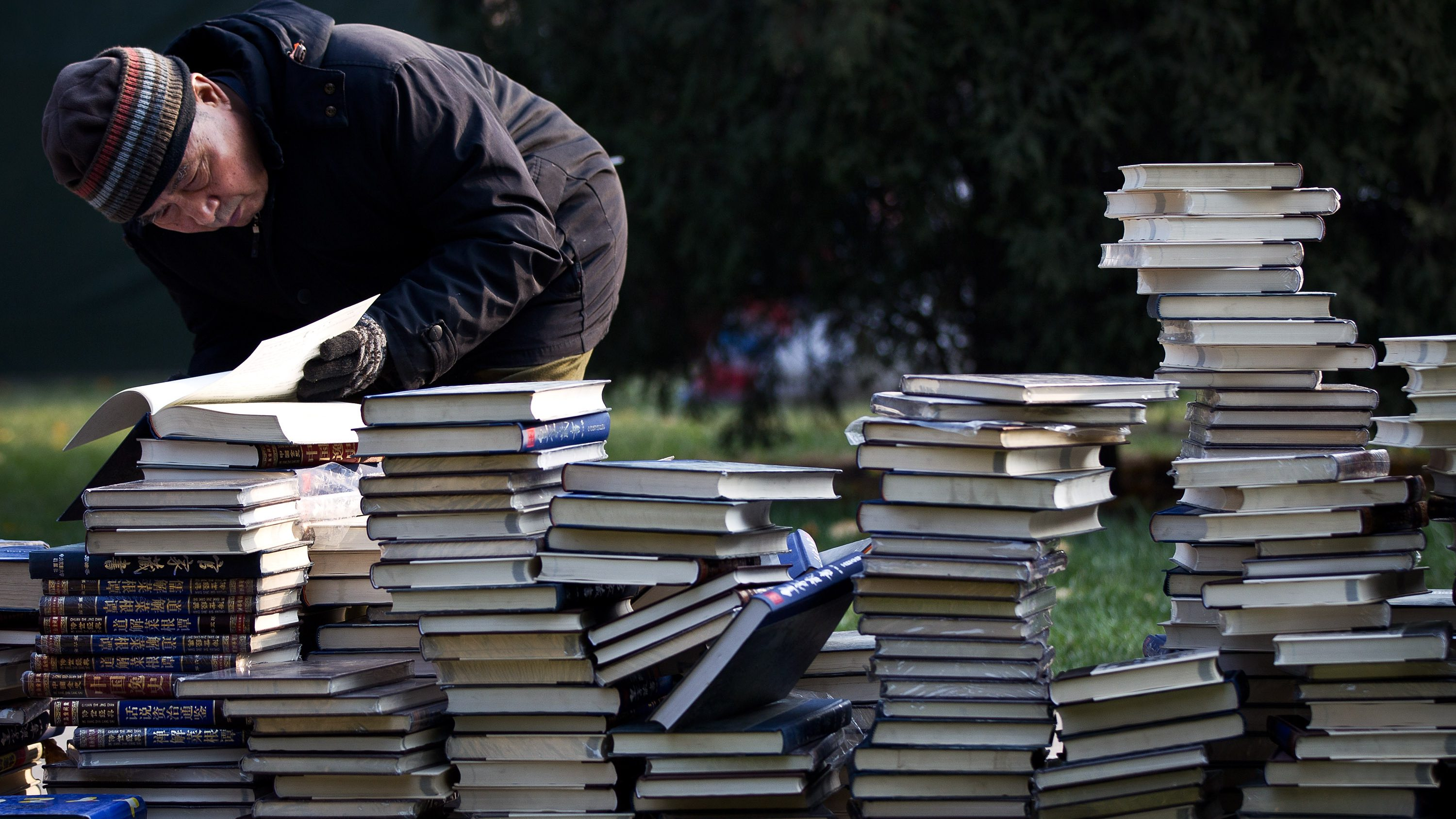 An elderly man browses one of books piled up on the grass for sale during the Winter Book Fair held at Ditan Park in Beijing, Sunday, Nov. 27, 2011. (AP Photo/Andy Wong)