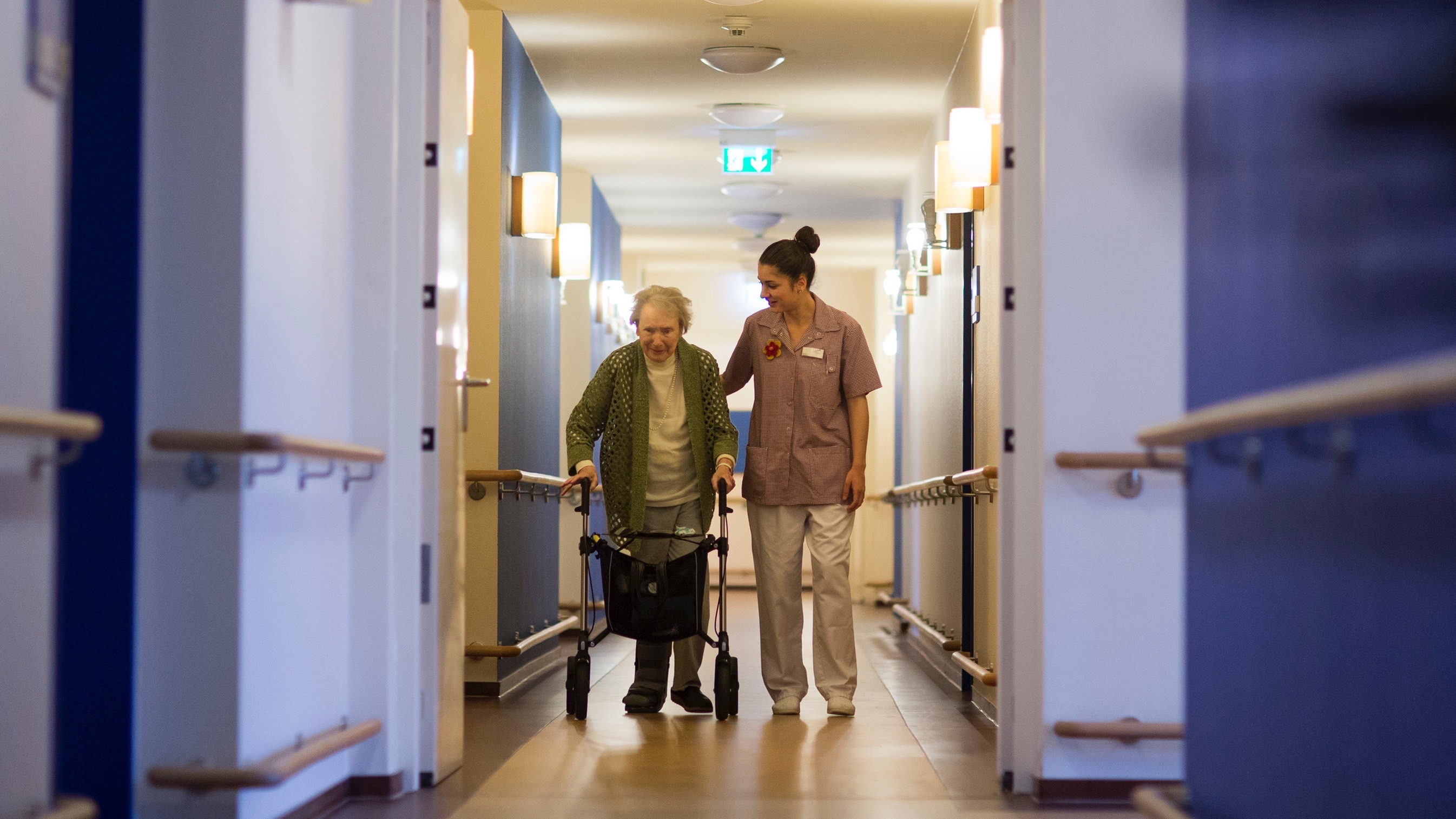 Raquel Lopez Leon from the Spanish city of Cordoba assists a resident on her way to lunch at the SenVital elderly home in Kleinmachnow outside Berlin May 28, 2013. Facing an acute shortage of skilled applicants among its own workforce, German institutions in the care sector increasingly turn to southern European countries to hire trained nursing staff who are willing to work abroad despite the language barrier in order to escape unemployment at home. The SenVital home for the elderly outside Berlin has accepted five qualified nurses from Spain as their staff, providing eight months of language training and additional care schooling needed to attain the German nursing concession.  Some 100 Spaniards applied for the ten vacancies SenVital had advertised across its various houses.  REUTERS/Thomas Peter (GERMANY ) - RTX103ZC
