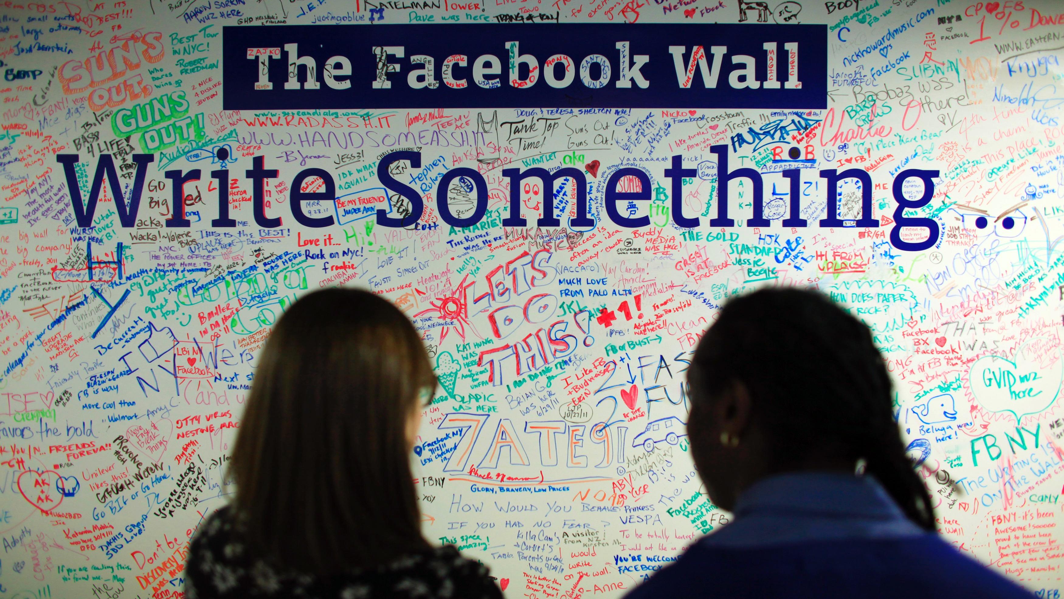 People look at the Facebook wall at their office in New York December 2, 2011.  REUTERS/Eduardo Munoz (UNITED STATES - Tags: BUSINESS) - RTR2URLD