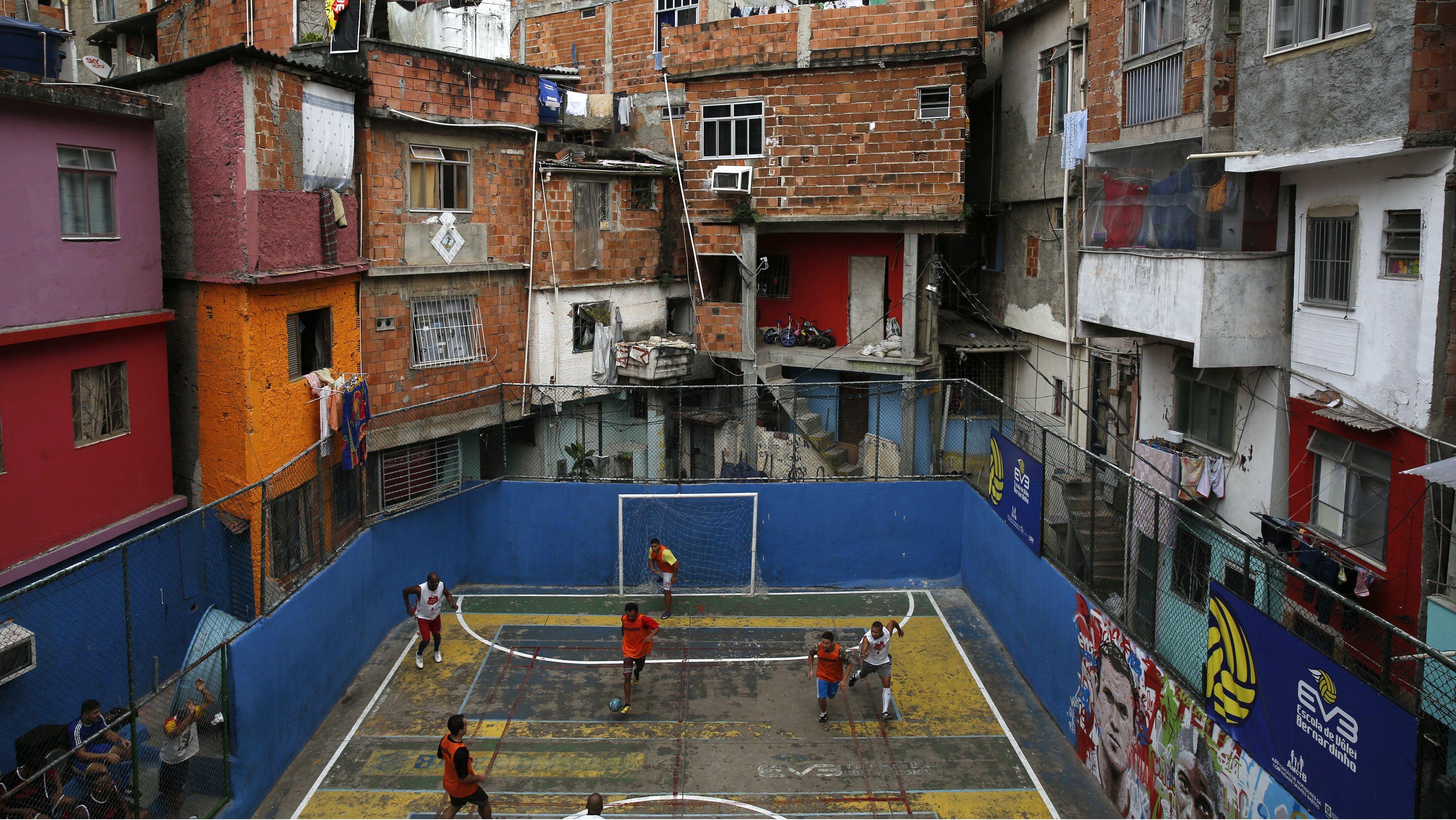 People take part in a soccer match held at the Tavares Bastos slum in Rio de Janeiro May 18, 2014. The World Cup will be held in 12 cities in Brazil from June 12 till July 13. REUTERS/Pilar Olivares (BRAZIL - Tags: SPORT SOCCER TPX IMAGES OF THE DAY)