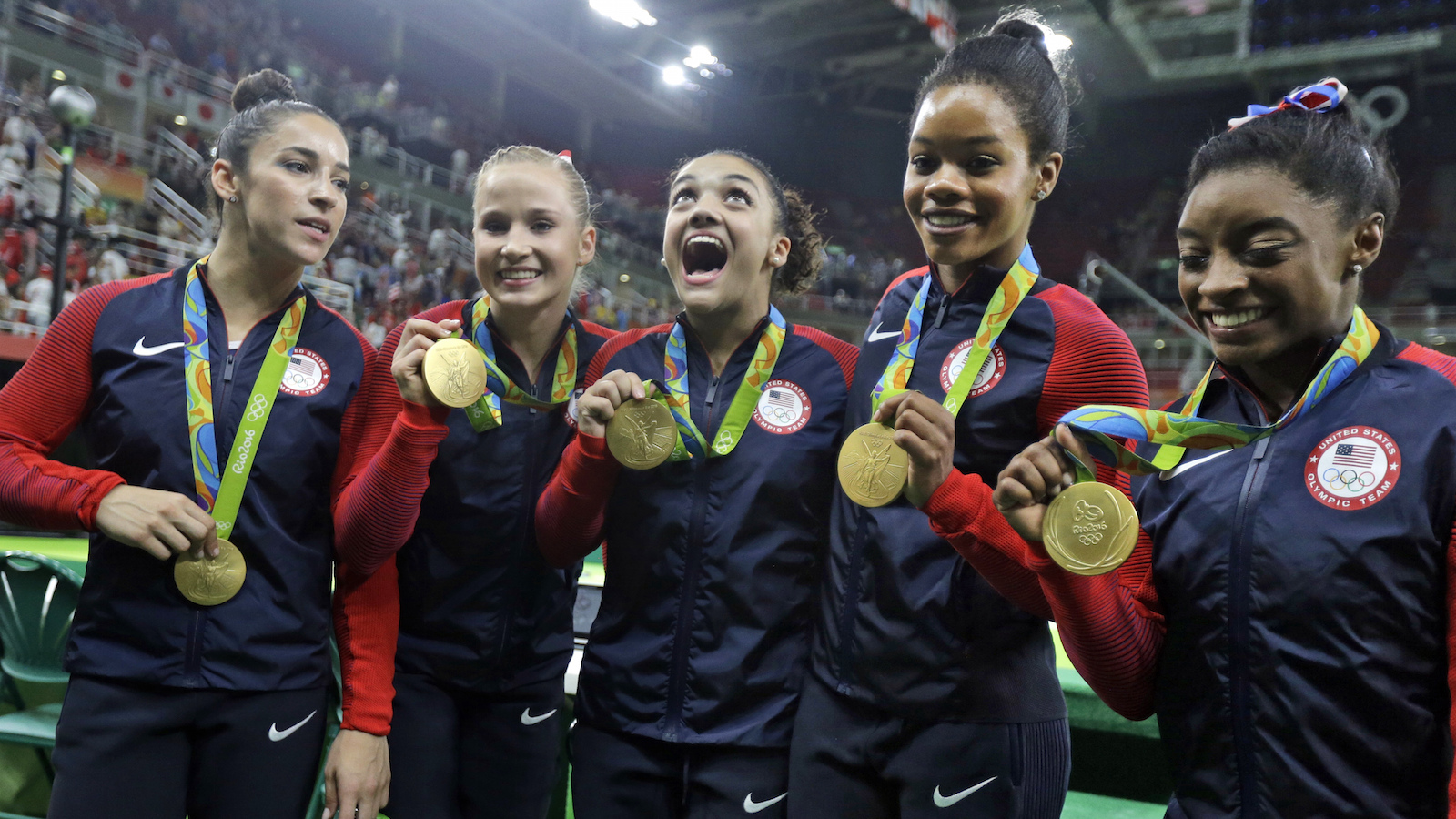 U.S. gymnasts and gold medallists, right to left, Simone Biles, Gabrielle Douglas, Lauren Hernandez, Madison Kocian and Aly Raisman pose for photographs during the medal ceremony for the artistic gymnastics women's team at the 2016 Summer Olympics in Rio de Janeiro, Brazil, Tuesday, Aug. 9, 2016. (AP Photo/Julio Cortez)
