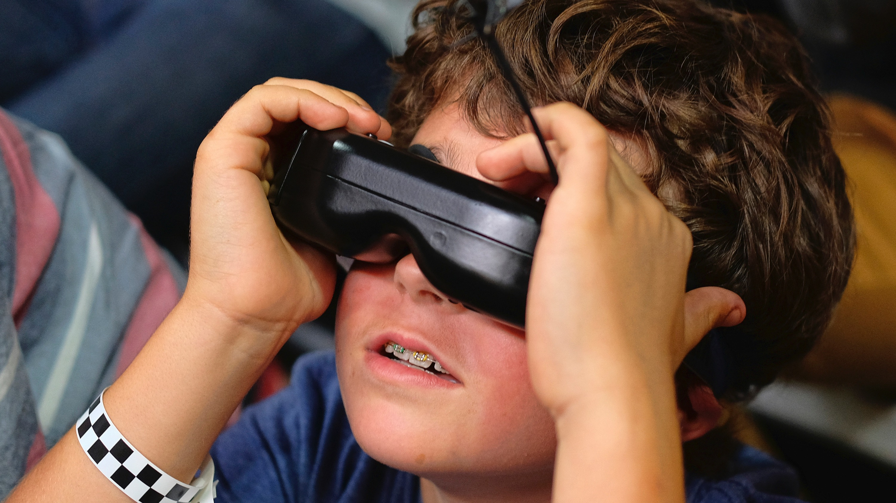 """HOLD FOR SWAYNE HALL IN BIZ-This March 19, 2016 photo shows Dashel Petranek,9, with strapped on First Person View goggles watches a drone racing during a race of the Drone Racing League in a vacant Hawthorne Plaza mall in Hawthorne, Calif. The DRL engineers its drones to be """"the size of dinner plates going 80 miles per hour,"""" said Horbaczewski. It hopes to be the Formula 1 of unmanned aerial vehicle racing. (AP Photo/Richard Vogel)"""