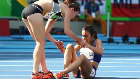 Abbey D'Agostino of the United States (R) is assisted by Nikki Hamblin of New Zealand after a collision during the a heat in the Women's 5000m at the Rio 2016 Olympics.
