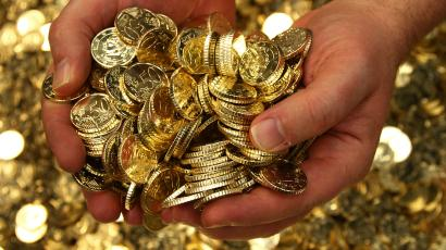 hands holding a pile of gold coins