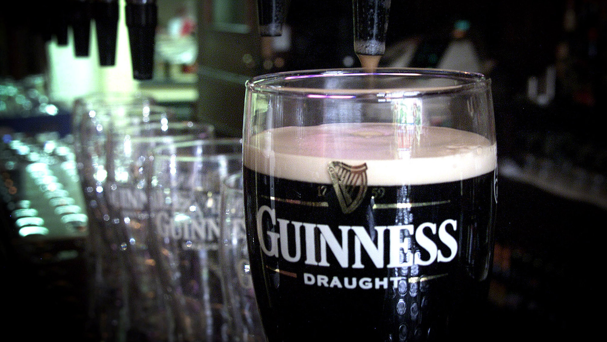Pint of Guinness next to more glasses
