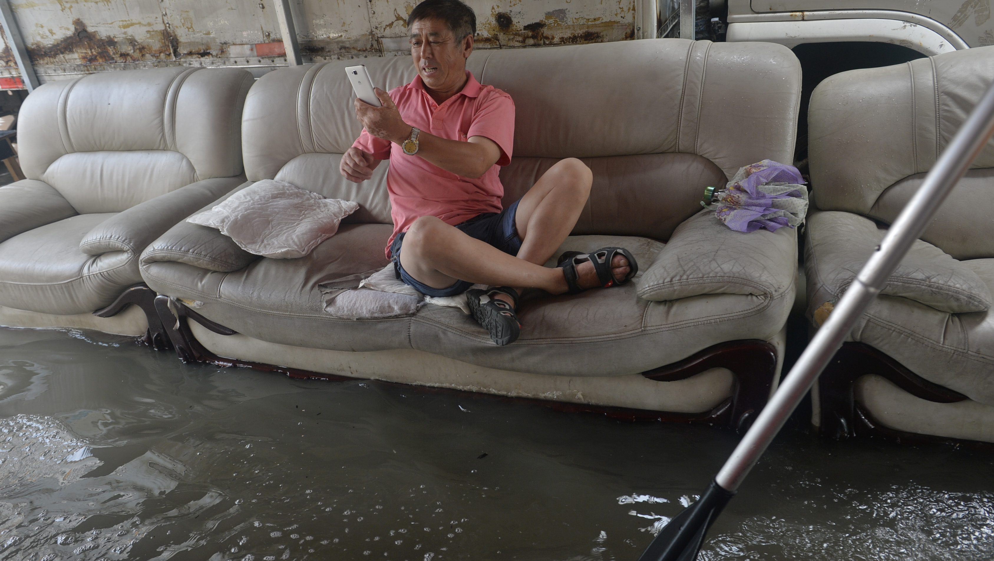 A man on a sofa takes photos of the flooding in Shenyang, Liaoning Province, northeast China, 25 July 2016.
