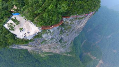epa05452645 A picture made available on 03 August 2016 shows an aerial view of tourists walking on a glass-bottomed skywalk on the Panlong (coiling dragon) Cliff on Tianmen Mountain in Zhangjiajie, Hunan Province, China, 01 August 2016. The 100-meter-long walk, giving a clear view of the deep valley behind, is the third glass walkway in the scenic zone. EPA/SHAO YING CHINA OUT
