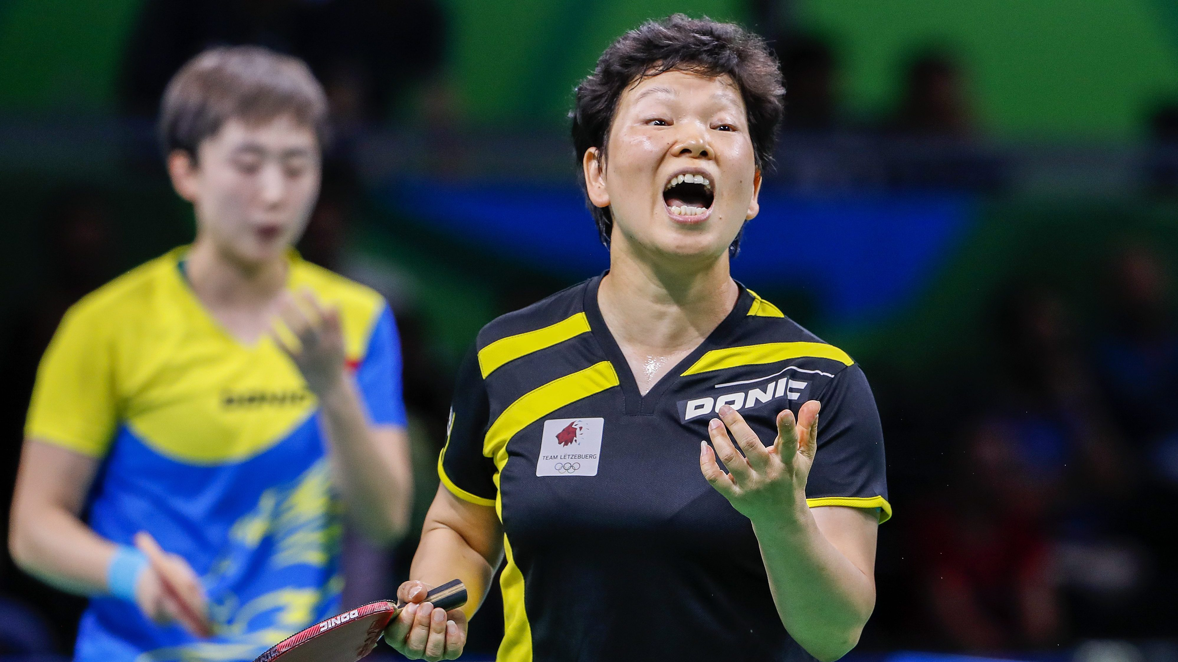 Xia Lian Ni (R) of Luxembourg reacts against Tianwei Feng (L) of Singapore during a third round Rio 2016 Olympic Games women's table tennis match, 8 August 2016.