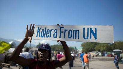 FILE PHOTO - A protester holds up a sign during a demonstration against the UN mission in downtown Port-au-Prince November 18, 2010. Reuters/Allison Shelley/File Photo