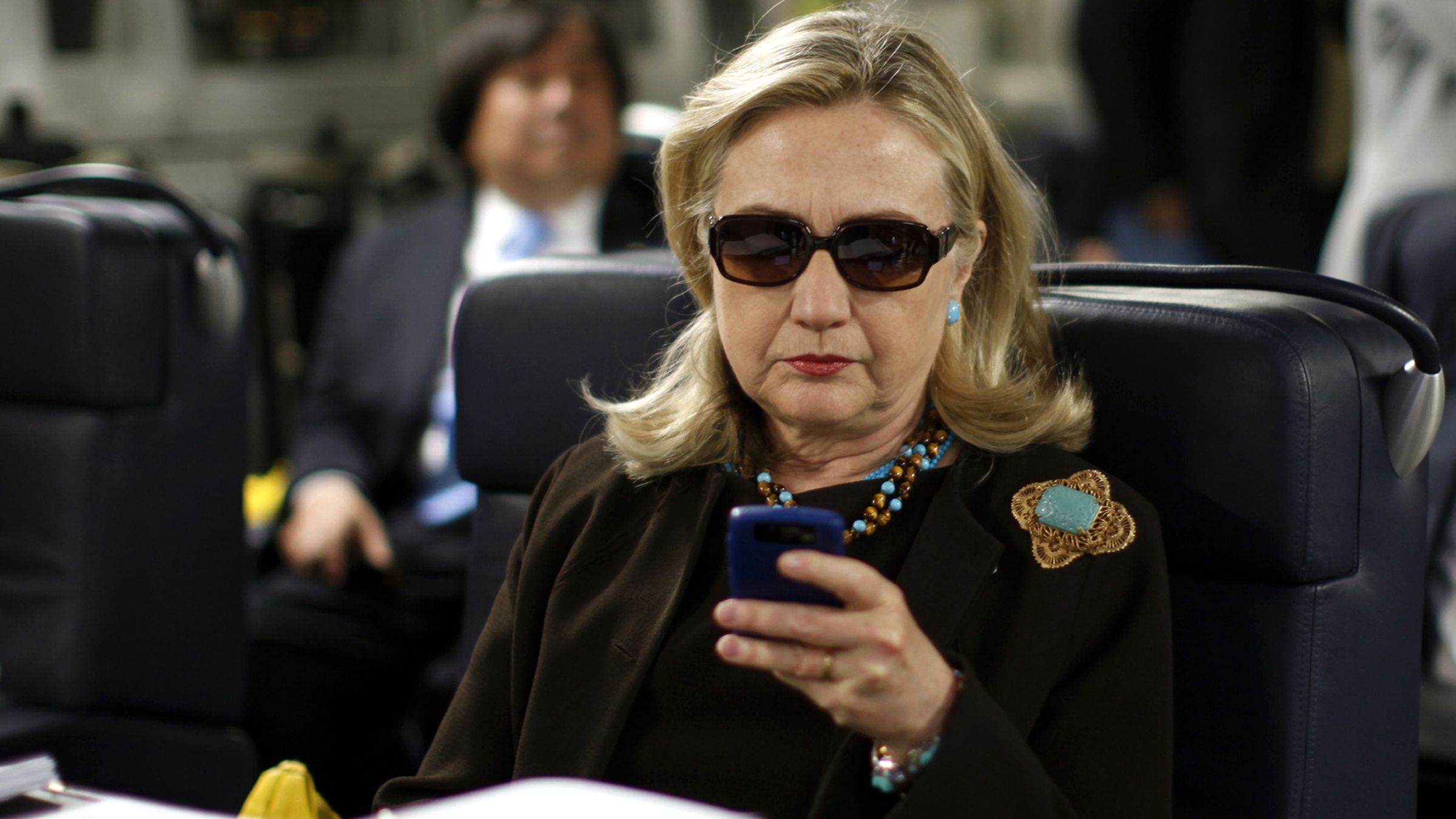 FILE - In this Oct. 18, 2011, file photo, then-Secretary of State Hillary Rodham Clinton checks her Blackberry from a desk inside a C-17 military plane upon her departure from Malta, in the Mediterranean Sea, bound for Tripoli, Libya. The State Department is reopening an internal investigation of possible mishandling of classified information by Hillary Clinton and top aides.