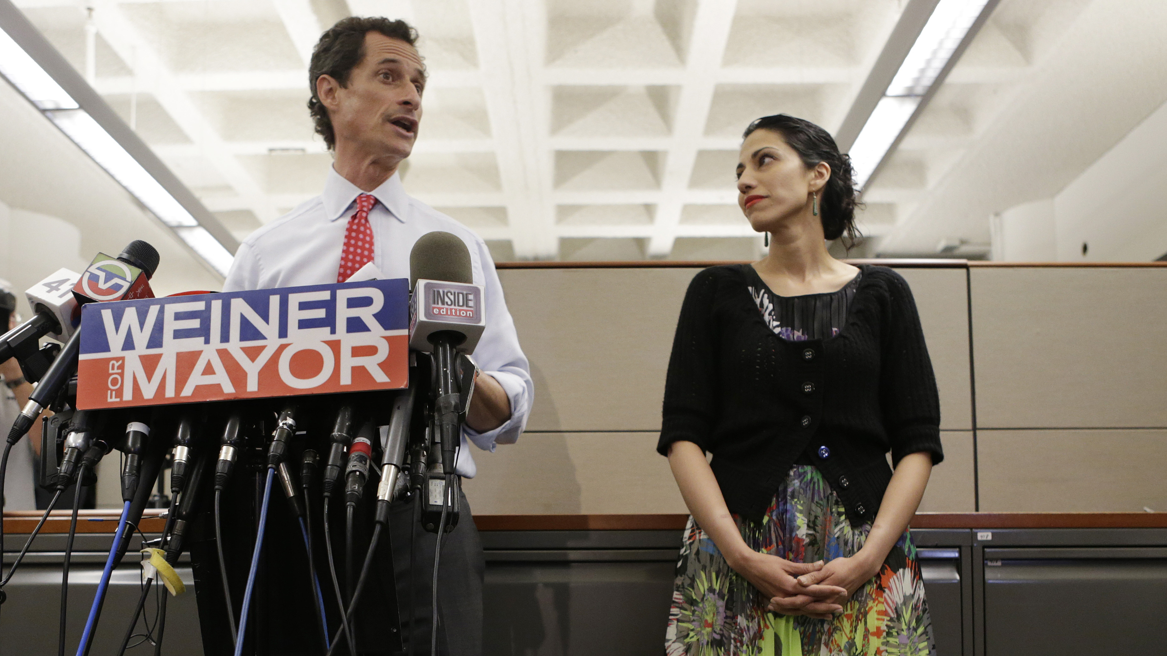 Huma Abedin, right, glances at her husband, New York City mayoral candidate Anthony Weiner as he speaks at a press conference at the Gay Men's Health Crisis, Tuesday, July 23, 2013, in New York. The former congressman says he's not dropping out of the New York City mayoral race in light of newly revealed explicit online correspondence with a young woman.