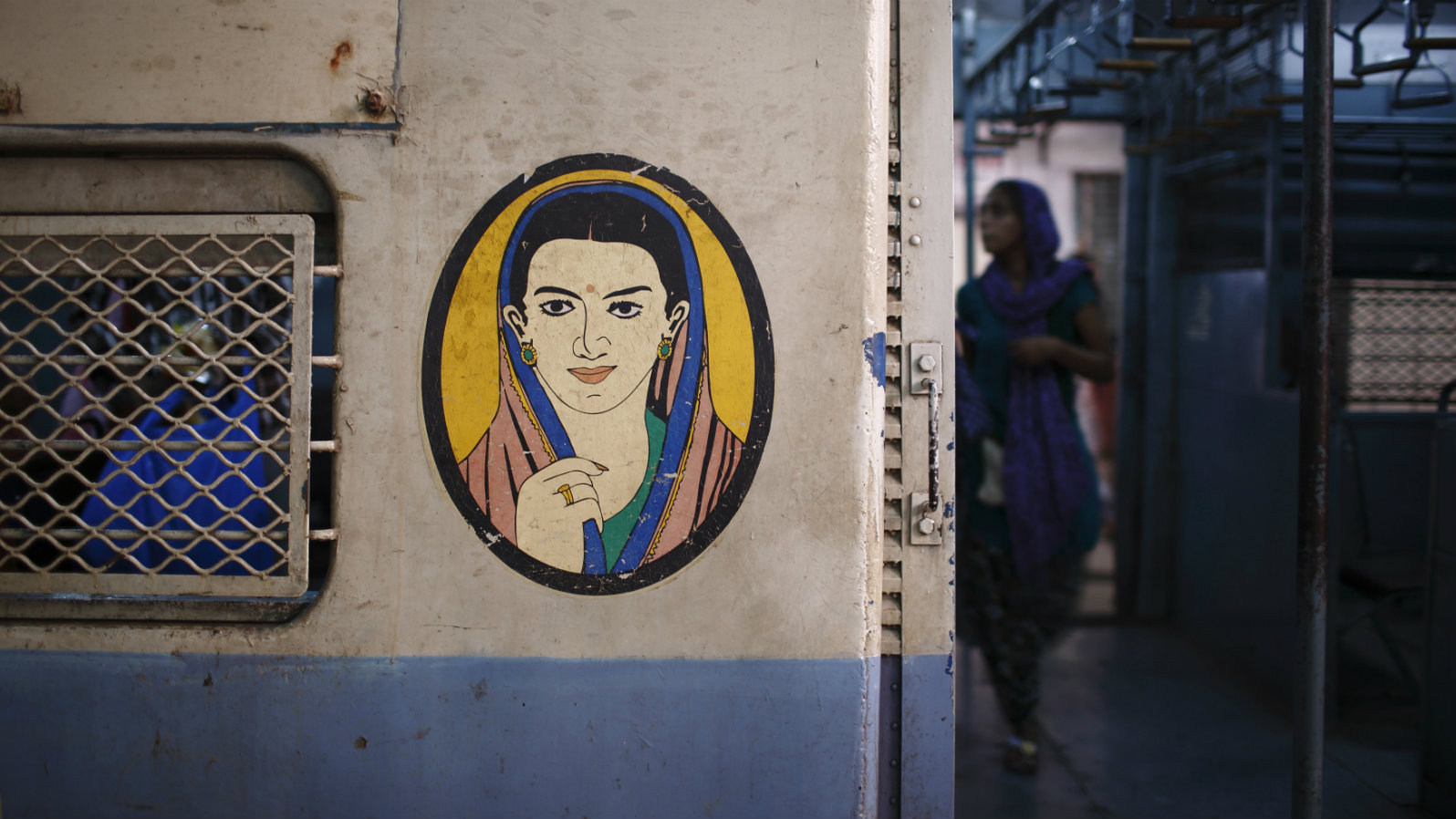 A portrait of a woman is seen near the entrance of the female compartment of a suburban train at Chhatrapati Shivaji Terminus Railway Station in Mumbai November 2, 2012. In India some train compartments, or sometimes whole trains, are reserved specifically for female passengers in an effort to make their travel easier and more secure. The role and treatment of women in society has recently become a hot political issue in the country, since the Dec. 16 gang rape of a 23-year-old student in New Delhi, who later died of her injuries, and whose case has led to widespread protests in the region against violence against women. Picture taken November 2, 2012.