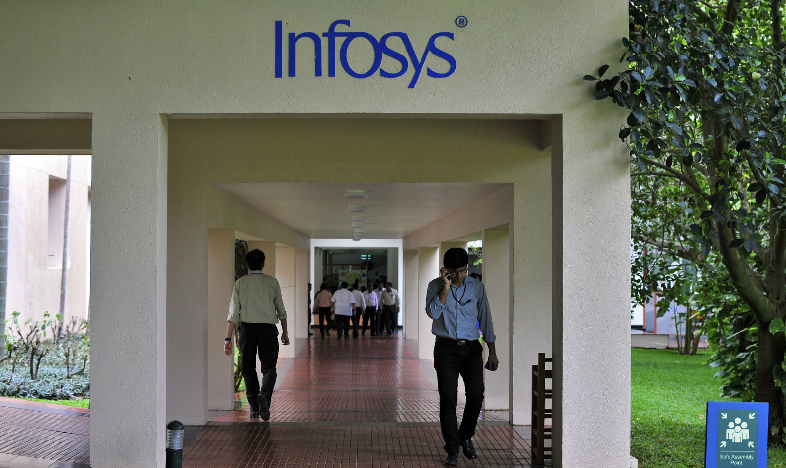 Employees walk along a corridor in the Infosys campus in the southern Indian city of Bangalore September 23, 2014. Infosys Ltd's new CEO Vishal Sikka has come up with a novel approach to reviving the financial fortunes of India's trailblazing outsourcing firm: use Facebook at work, tweet, but get the job done. Infosys has long been run as a conservative company known for keeping strict tabs on work hours and sometimes fining employees for not wearing ties on specific days. Such cheerless self-regard could not have come at a more challenging time, analysts say. To retain talent, Sikka hopes to create a more employee-friendly workplace. To match story INFOSYS-CEO/STRATEGY
