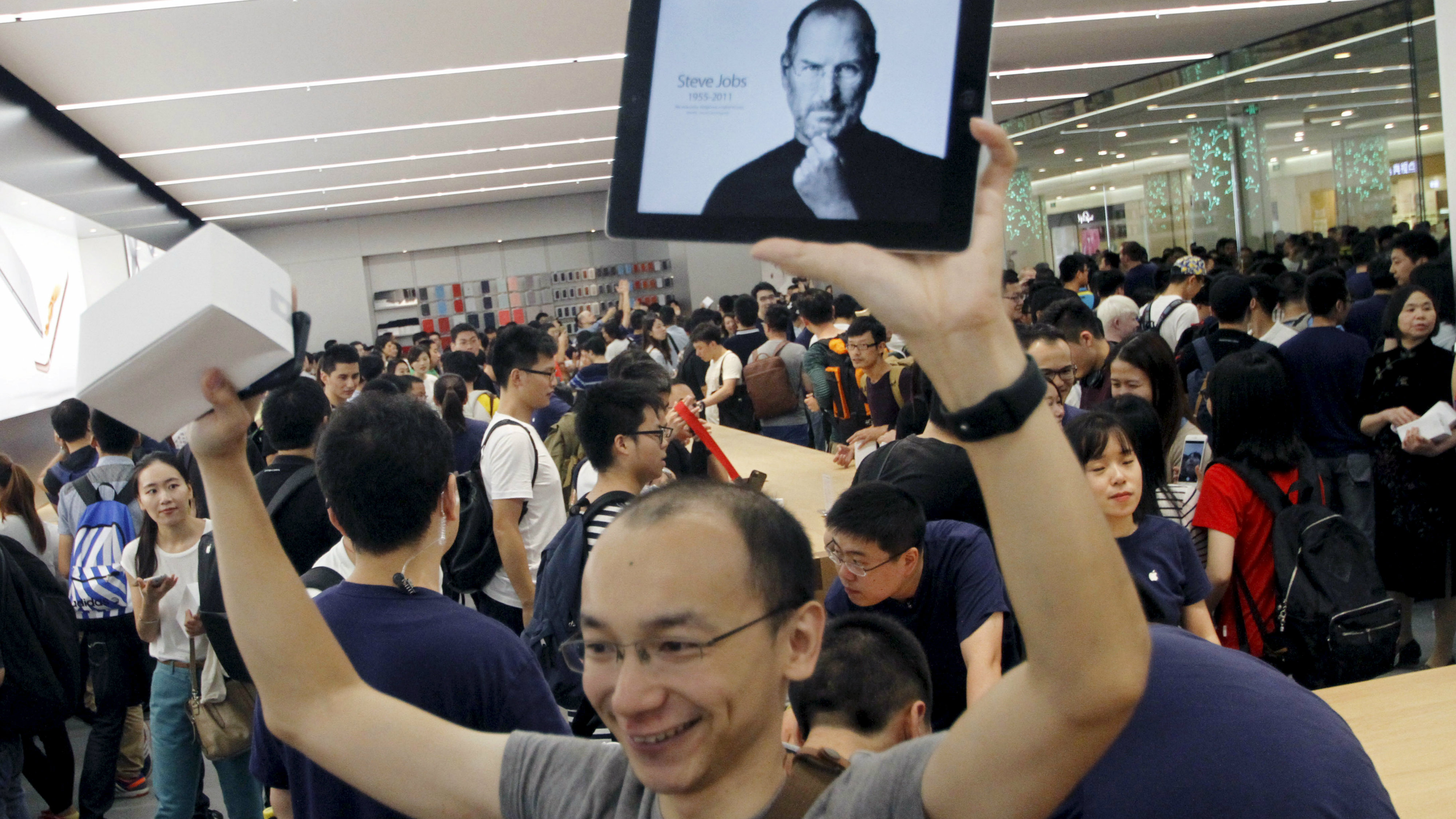 A customer holds an iPad displaying a picture of Steve Jobs, during the opening of a new Apple Store in Nanjing, Jiangsu province, September 19, 2015. Picture taken September 19, 2015. REUTERS/Stringer CHINA OUT. NO COMMERCIAL OR EDITORIAL SALES IN CHINA