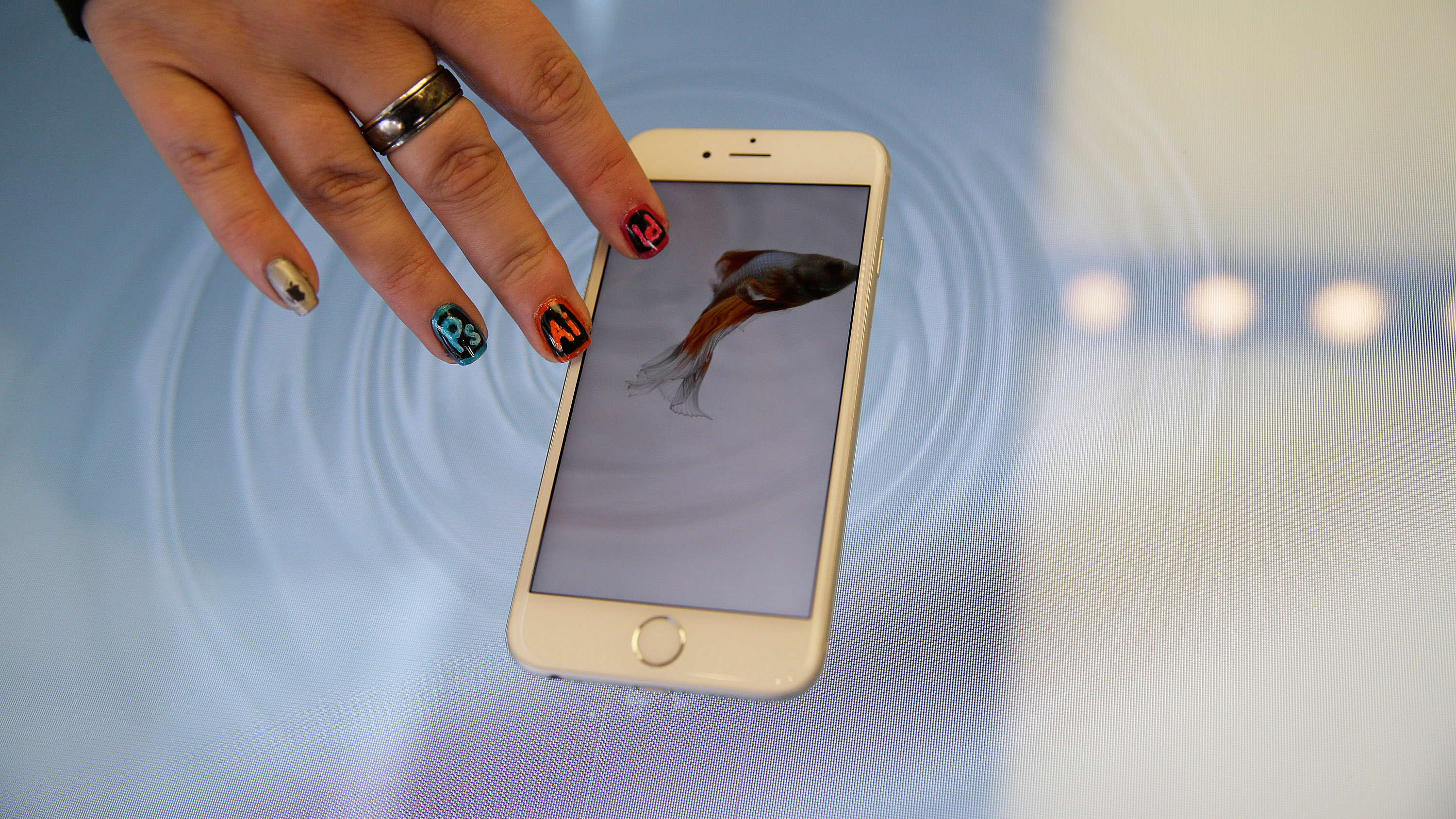 A woman press an Apple iPhone 6s on a 3D touch table at the Apple store Friday, Nov. 13, 2015, in San Francisco. The table allows people to get a better sense of the touch capabilities of the phone. (AP Photo/Eric Risberg)