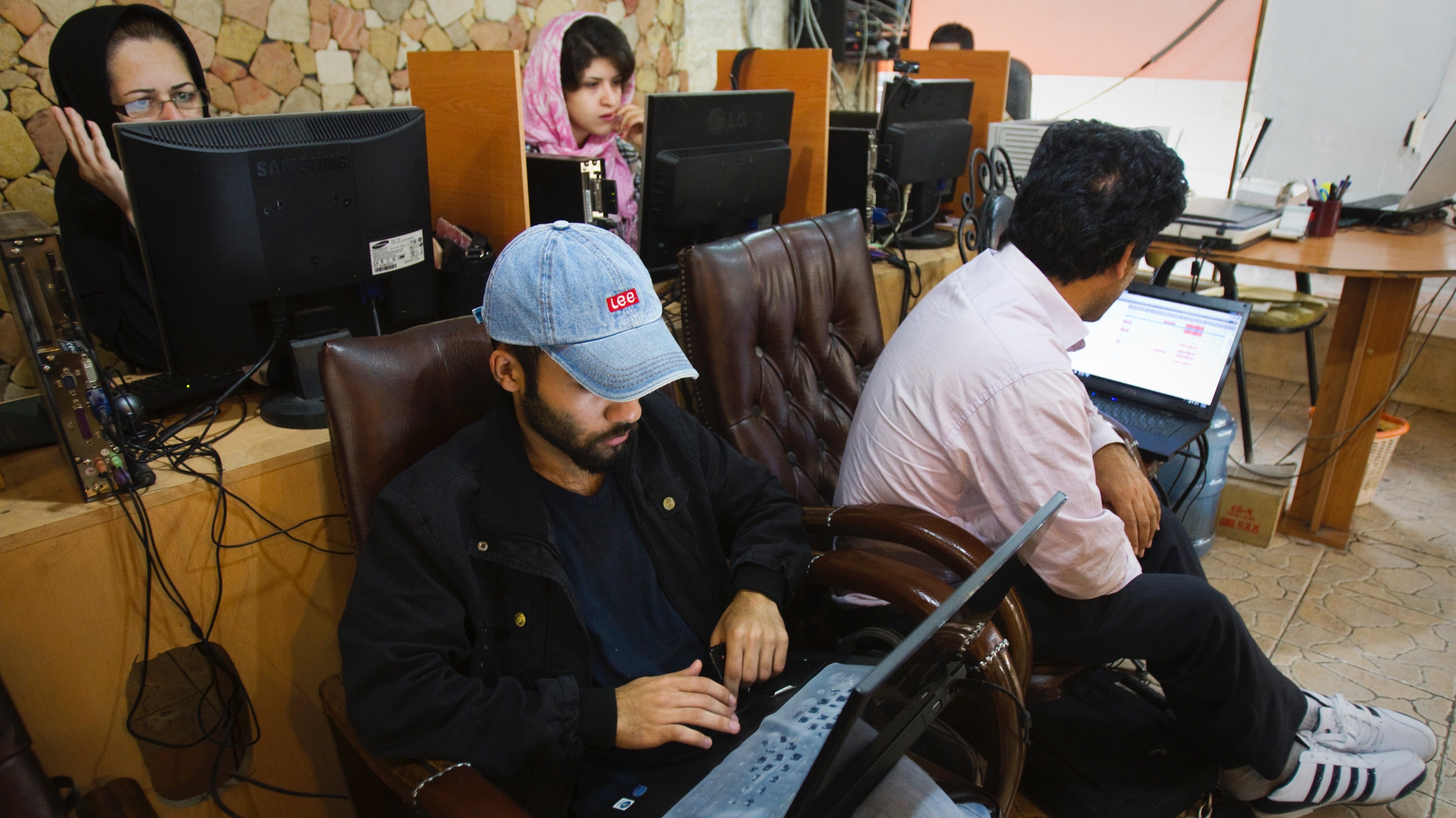 """Customers use computers at an internet cafe in Tehran May 9, 2011. Websites like Facebook, Twitter, YouTube and countless others were banned shortly after the re-election of Iran's President Mahmoud Ahmadinejad and the huge street protests that followed. Seen by the government as part of a """"soft war"""" waged by the enemies of the Islamic Republic, social networking and picture sharing sites were a vital communication tool for the anti-Ahmadinejad opposition -- more than a year before they played a similar role in the popular uprisings that toppled Arab dictatorships in Tunisia and Egypt. In Iran, trying to access Facebook on a normal Internet line will redirect the user to a filter page, which says blocked sites are those considered criminal, that offend """"Islamic sanctities"""" or insult public and government officials. But, for many Iranians, bypassing the government filter is as easy as switching on the computer. Picture taken May 9, 2011.   To match Feature IRAN-INTERNET/         REUTERS/Raheb Homavandi (IRAN - Tags: MEDIA SOCIETY SCI TECH POLITICS) - RTR2MB5Q"""