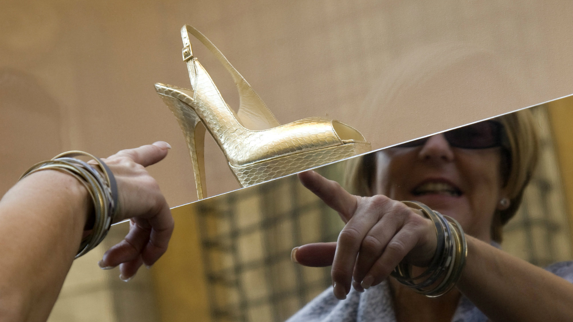 woman pointing at Jimmy Choo shoe in a window