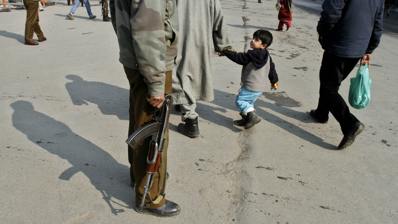 A Kashmiri boy passes by an Indian paramilitary soldier in Srinagar.