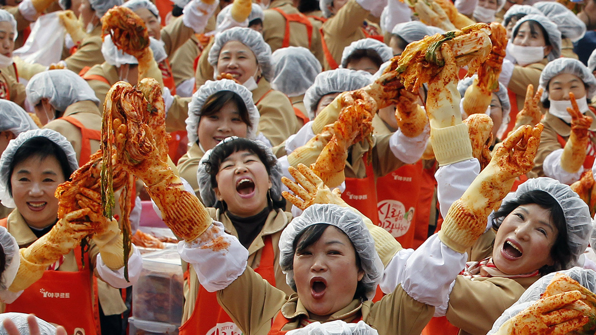 "Women make a traditional Korean side dish ""kimchi"" or fermented cabbage, at a charity event at the Seoul City Hall Plaza November 8, 2011. About 2,000 volunteers made 270 tonnes of kimchi on Tuesday to give away to needy people during the winter season. REUTERS/Jo Yong-Hak (SOUTH KOREA - Tags: SOCIETY FOOD TPX IMAGES OF THE DAY)"
