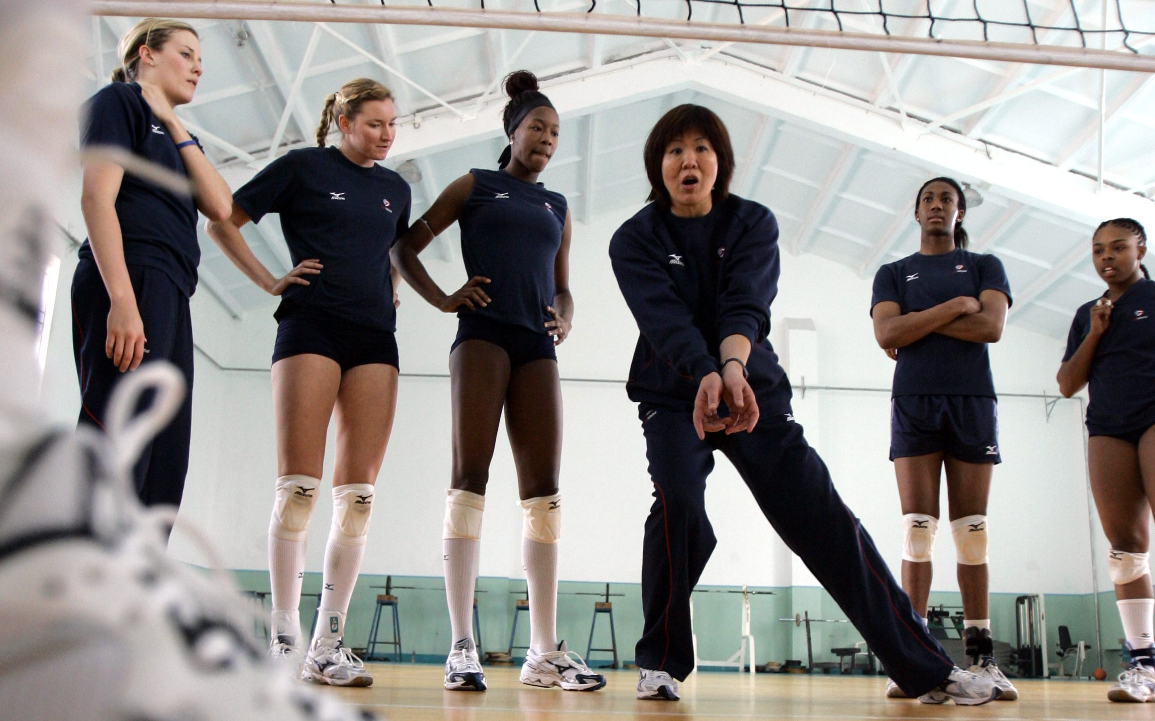 Team USA women's volleyball coach Jenny Lang Ping, of China, fourth from left, instructs her players during a workout, Wednesday, March 19, 2008, in Tianjin, China. Players, from left, Tracy Stalls, Angie McGinnis, Destinee Hooker, Foluke Akinredewo, and,  Therese Crawford, listen to Lang Ping.
