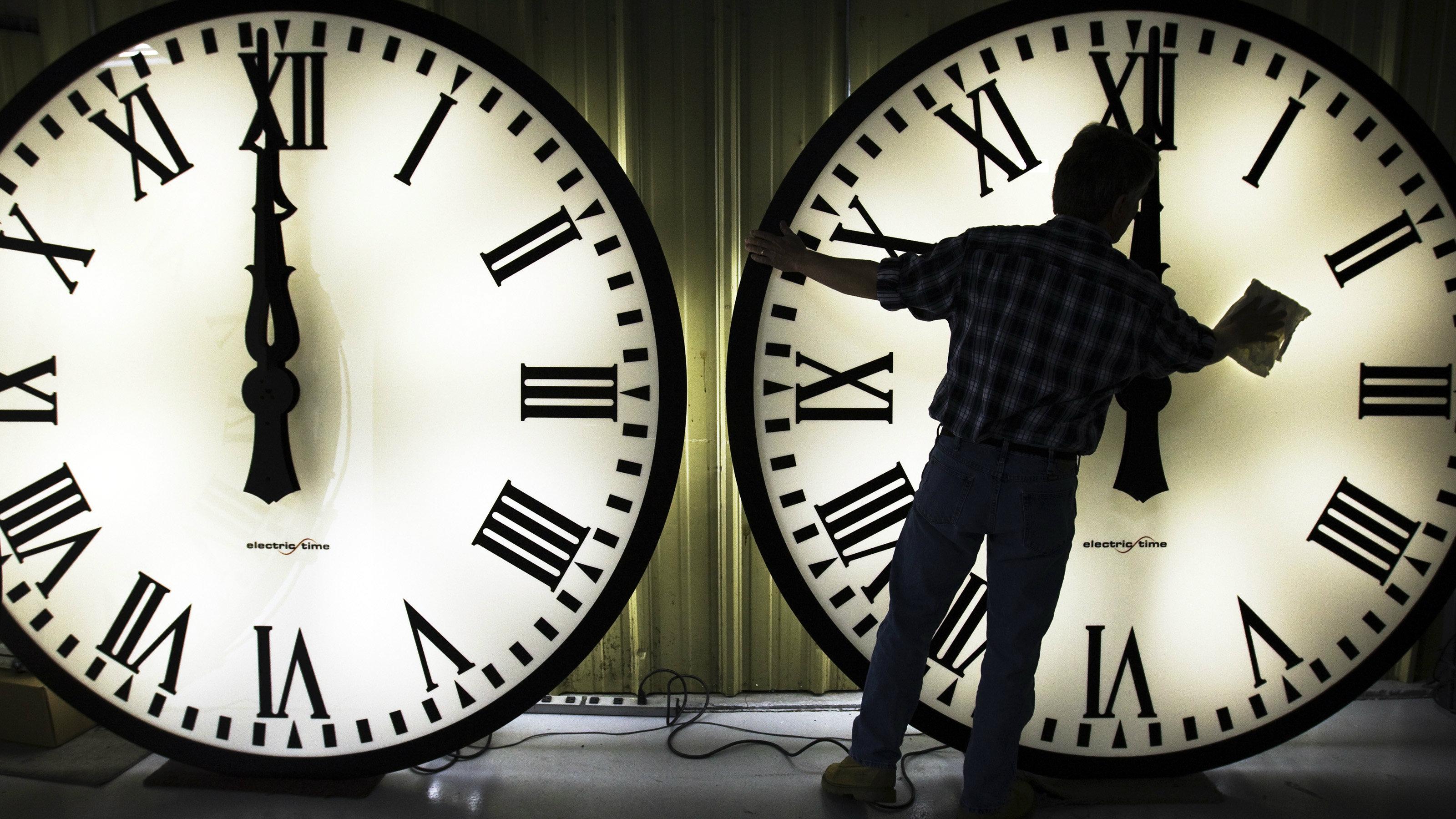 A man cleaning clocks