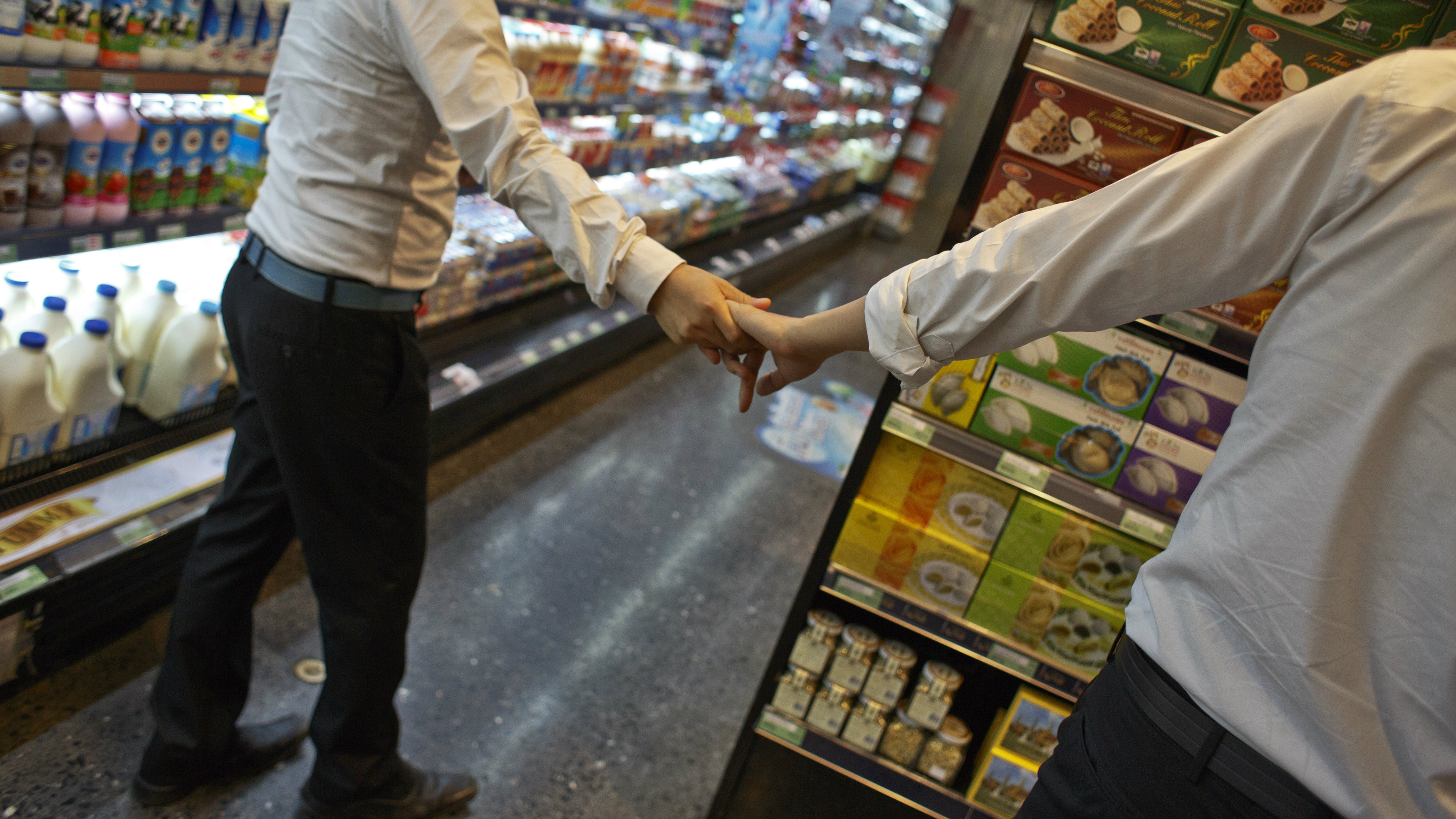 Men holding hands in grocery store