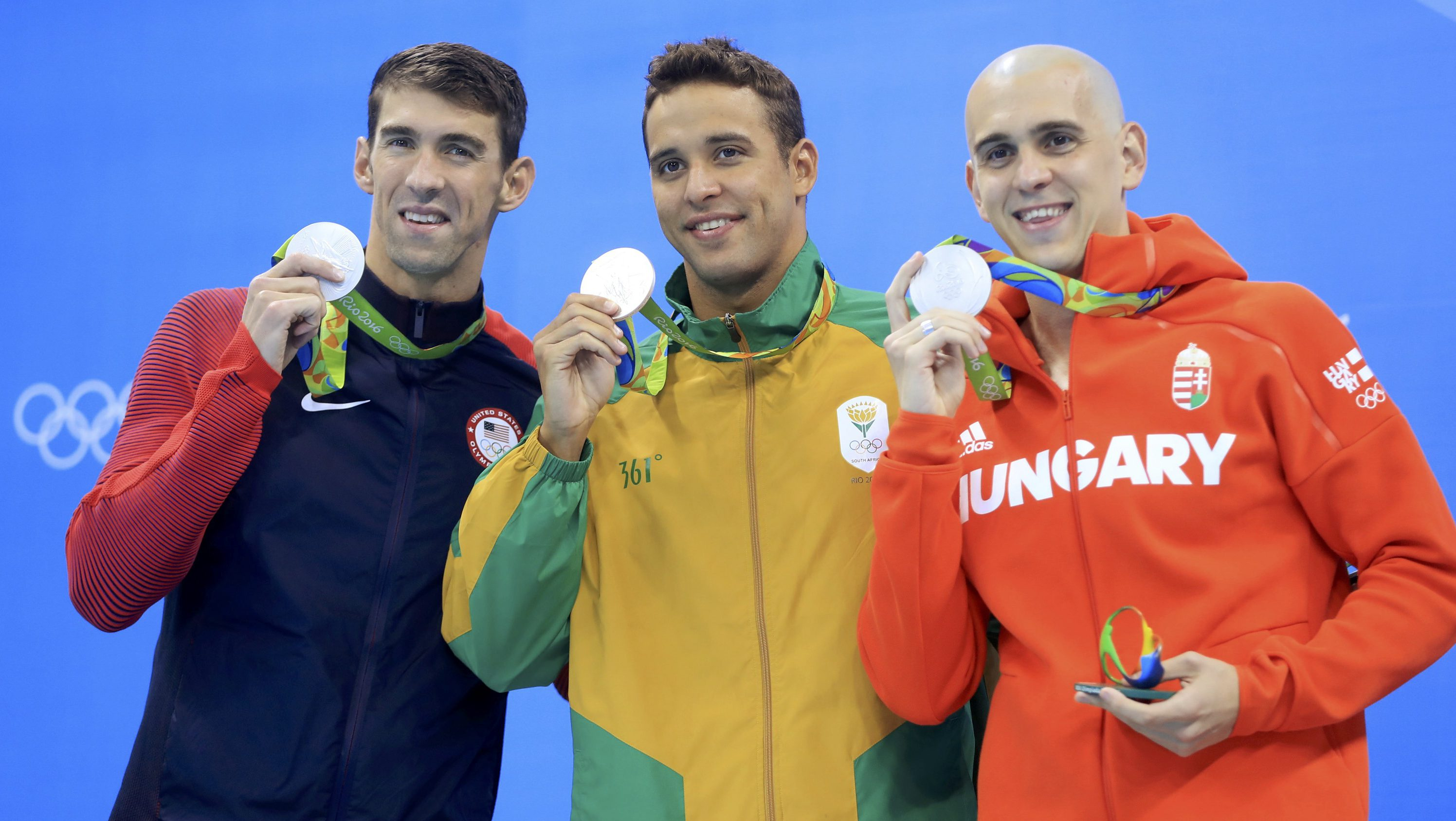 Swimmers Michael Phelps, Chad le Clos, and Laszlo Cseh hold up their silver medals in a three-way tie at the Olympics.